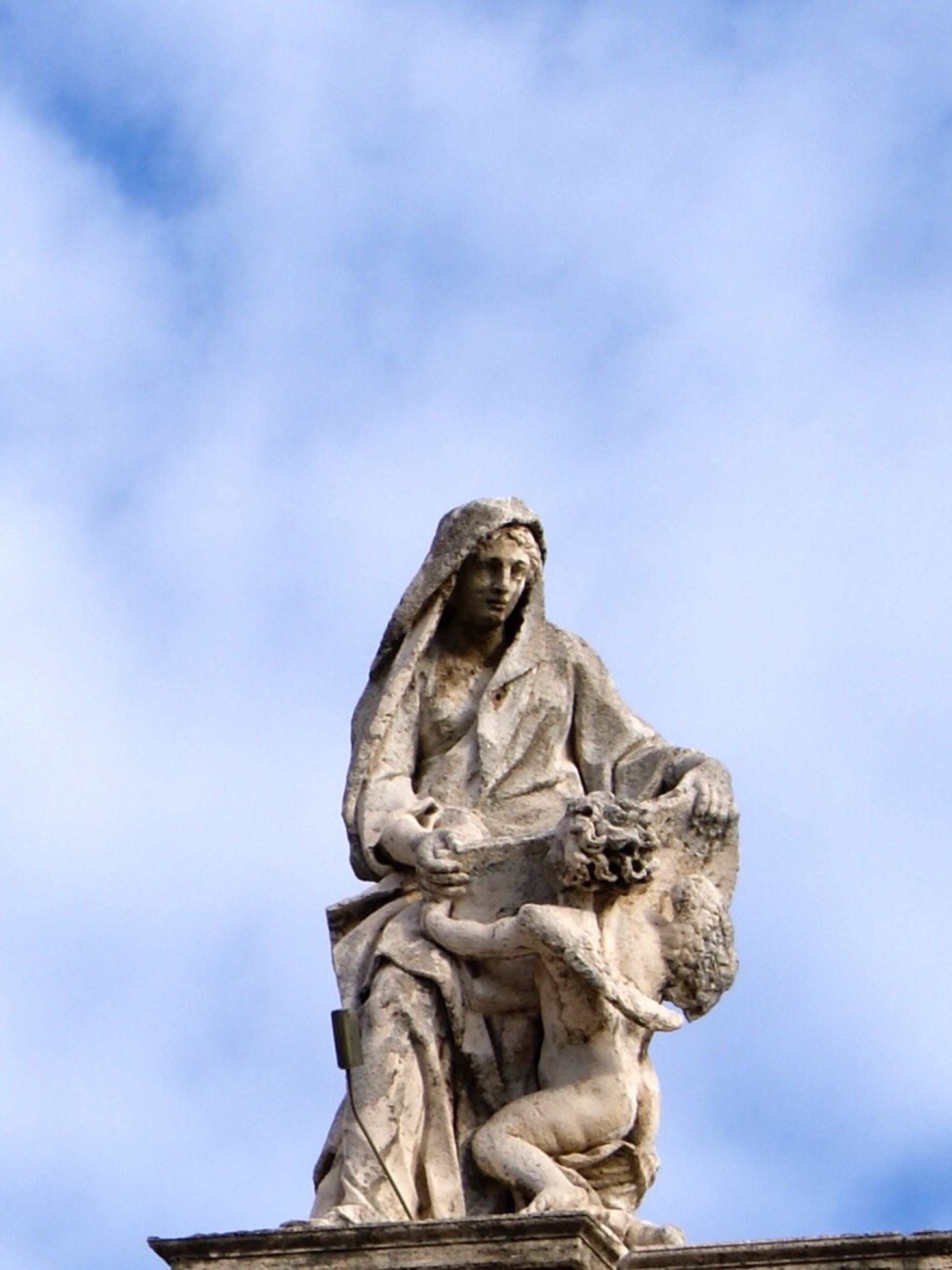 statue, sculpture, human representation, low angle view, art and craft, art, sky, creativity, cloud - sky, cloud, animal representation, outdoors, no people, cloudy, day, carving - craft product, angel, monument