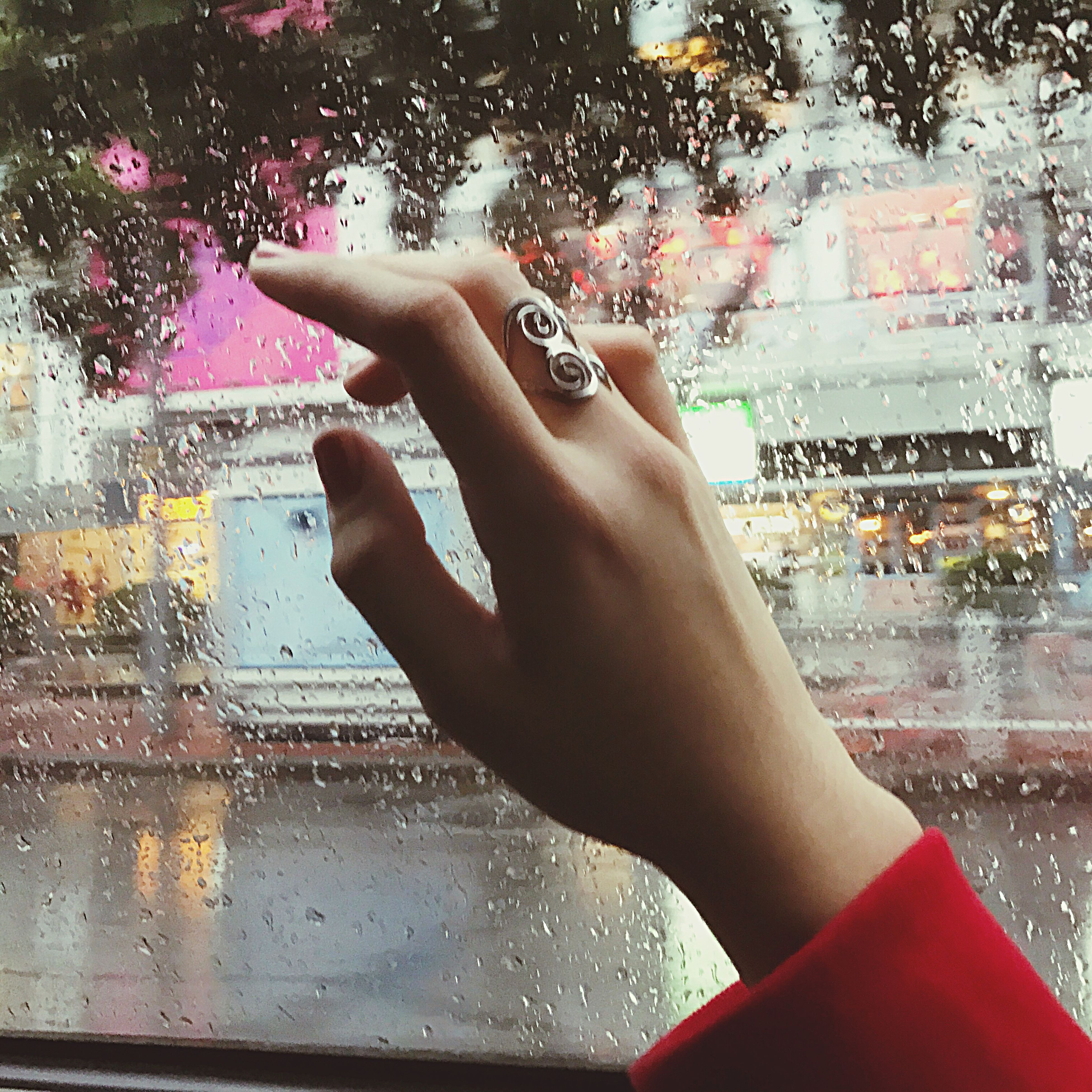 glass - material, human hand, window, human body part, transparent, vehicle interior, lifestyles, drop, wet, windshield, leisure activity, looking through window, real people, rain, close-up, one person, car interior, rainy season, holding, water, day, adults only, sky, raindrop, people, indoors, adult
