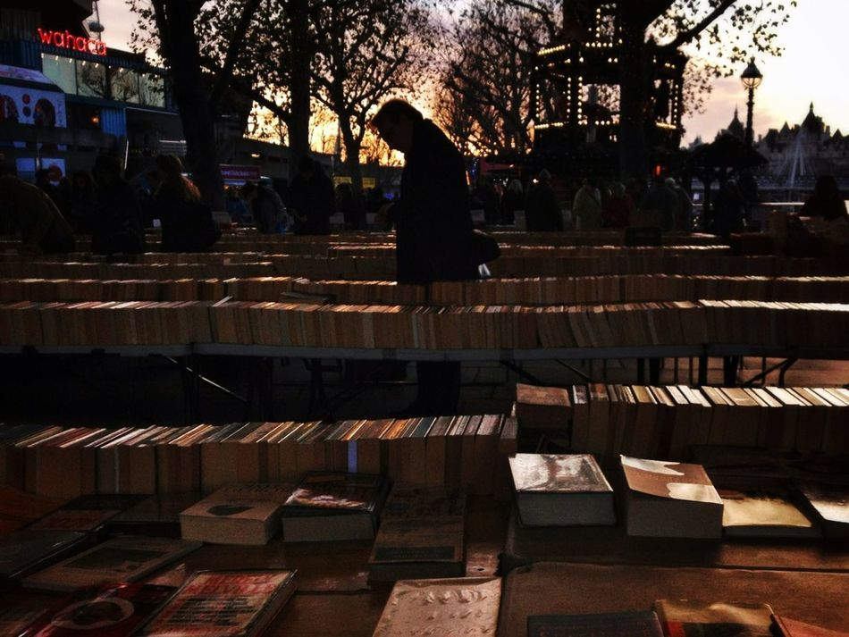 A man reads at a second hand book stall as the sun sets near Waterloo in London