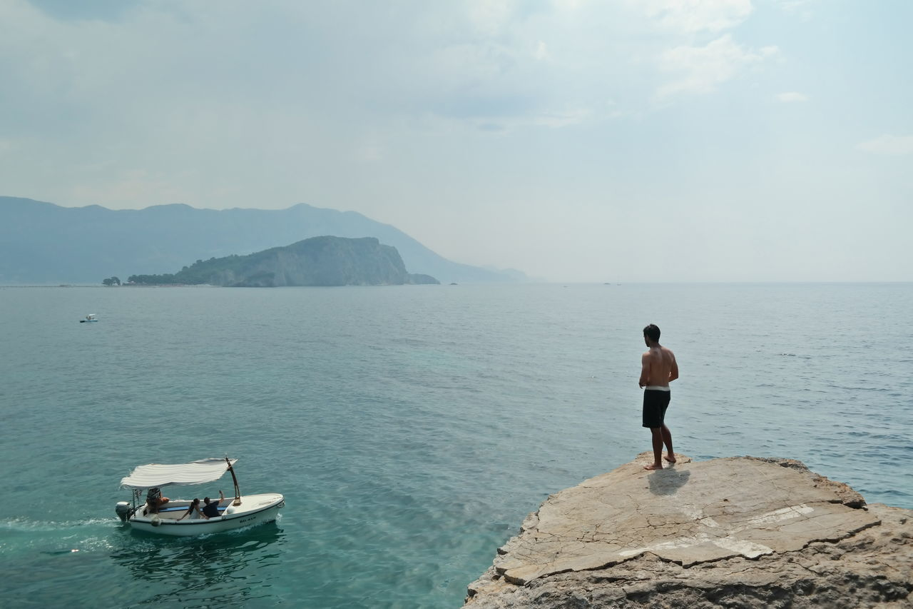 Rear View Of Shirtless Man Overlooking Calm Sea