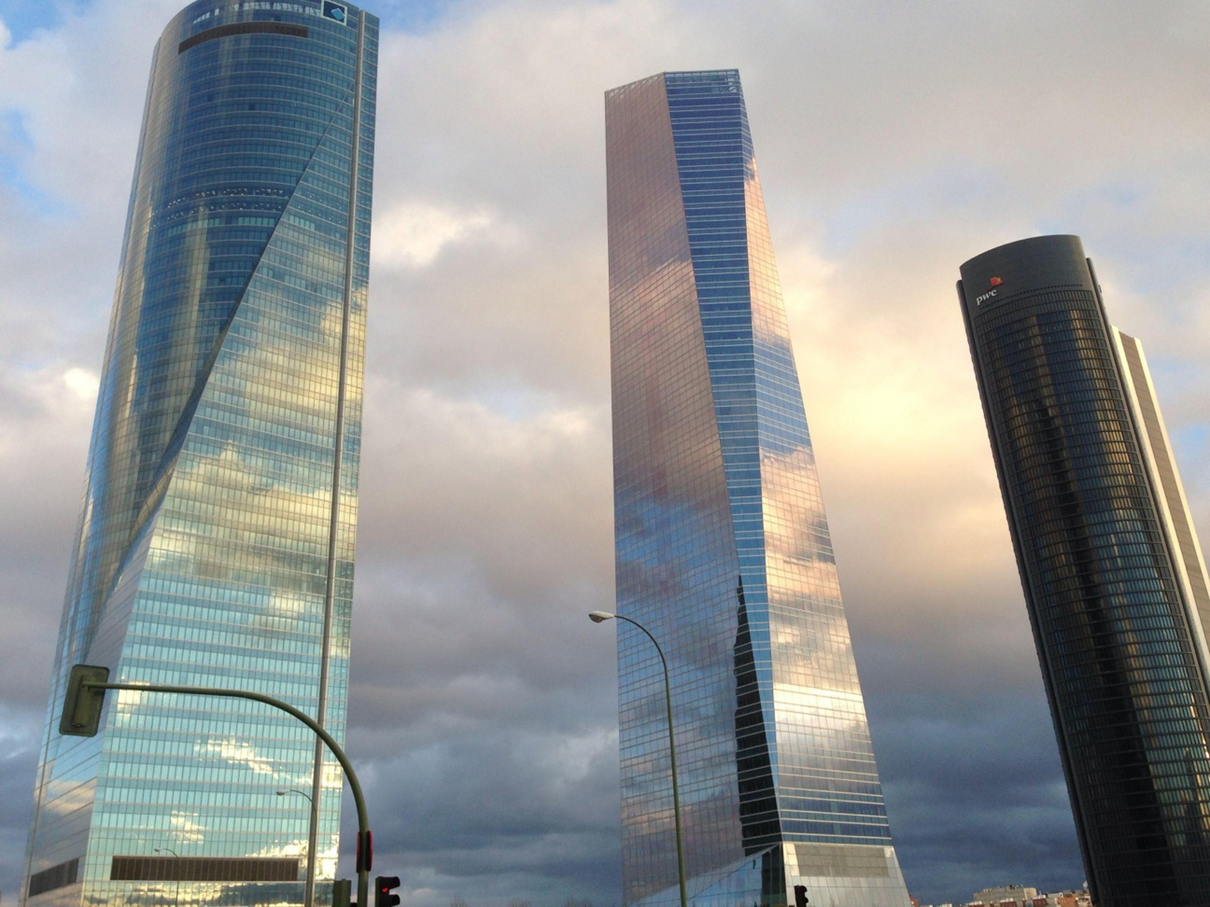 skyscraper, architecture, building exterior, built structure, modern, tall - high, low angle view, office building, sky, city, tower, cloud - sky, cloudy, cloud, tall, building, glass - material, capital cities, financial district, urban skyline