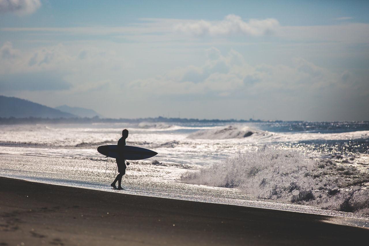 Silhouette Of Surfer On Beach Against Sky