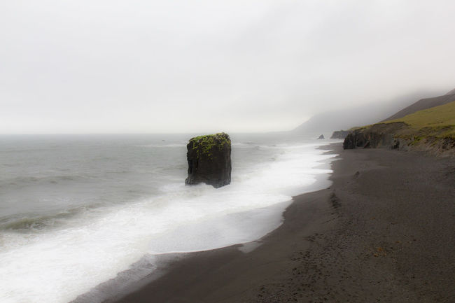Dyrhólaey - Iceland Adventure Beach Beauty In Nature Coastline Dyrhólaey Fog Horizon Over Water Ice Iceland Journey Landscape Monolith Nature Outdoors Panorama Reef Rock Formation Sea Shore The Great Outdoors With Adobe Travel Travel Destinations Water Wave Wind
