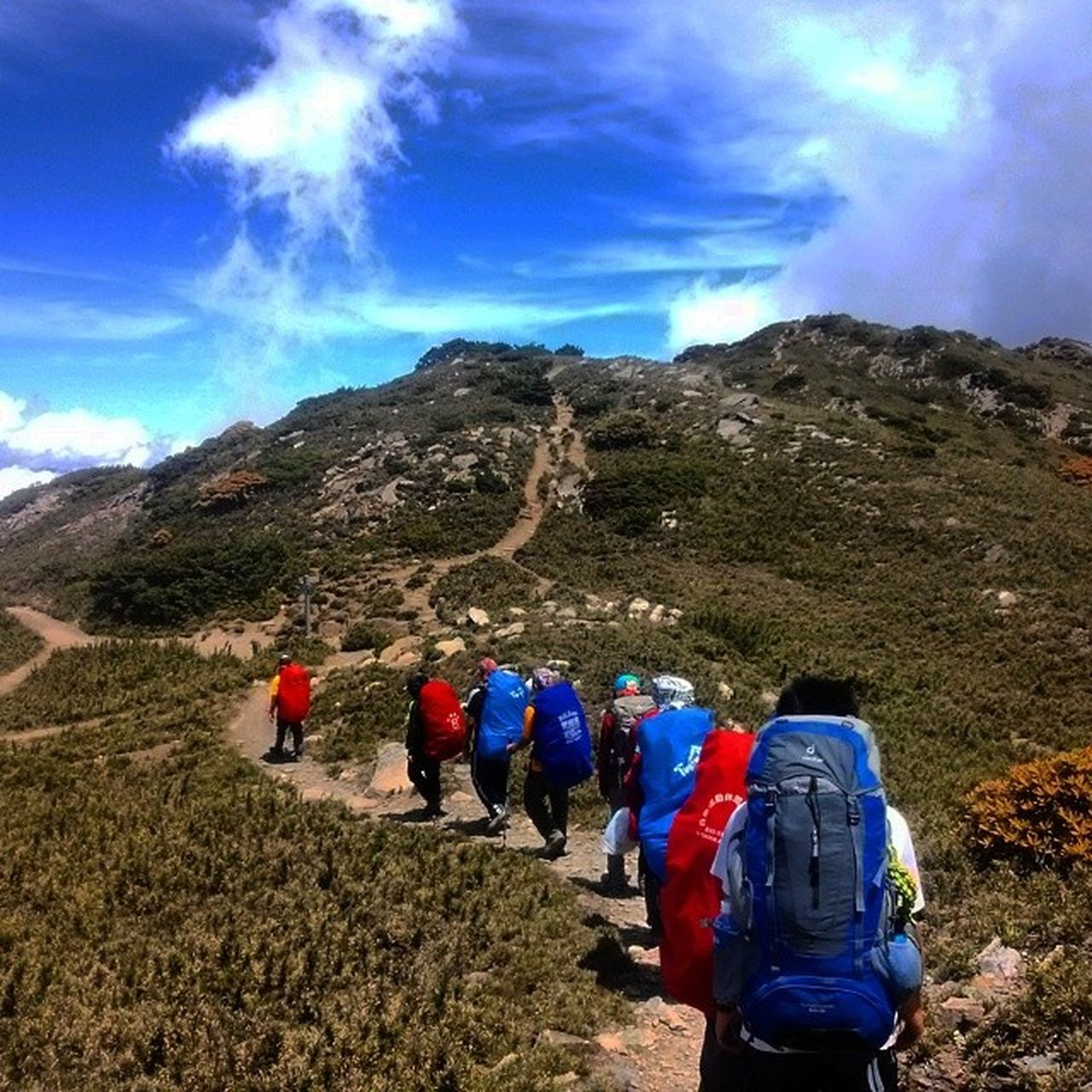 real people, mountain, adventure, hiking, sky, walking, backpack, nature, rear view, hiker, leisure activity, landscape, exploration, lifestyles, beauty in nature, day, men, outdoors, cloud - sky, women, blue, climbing, togetherness, low angle view, scenics, vacations, mountain range, group of people, grass, people