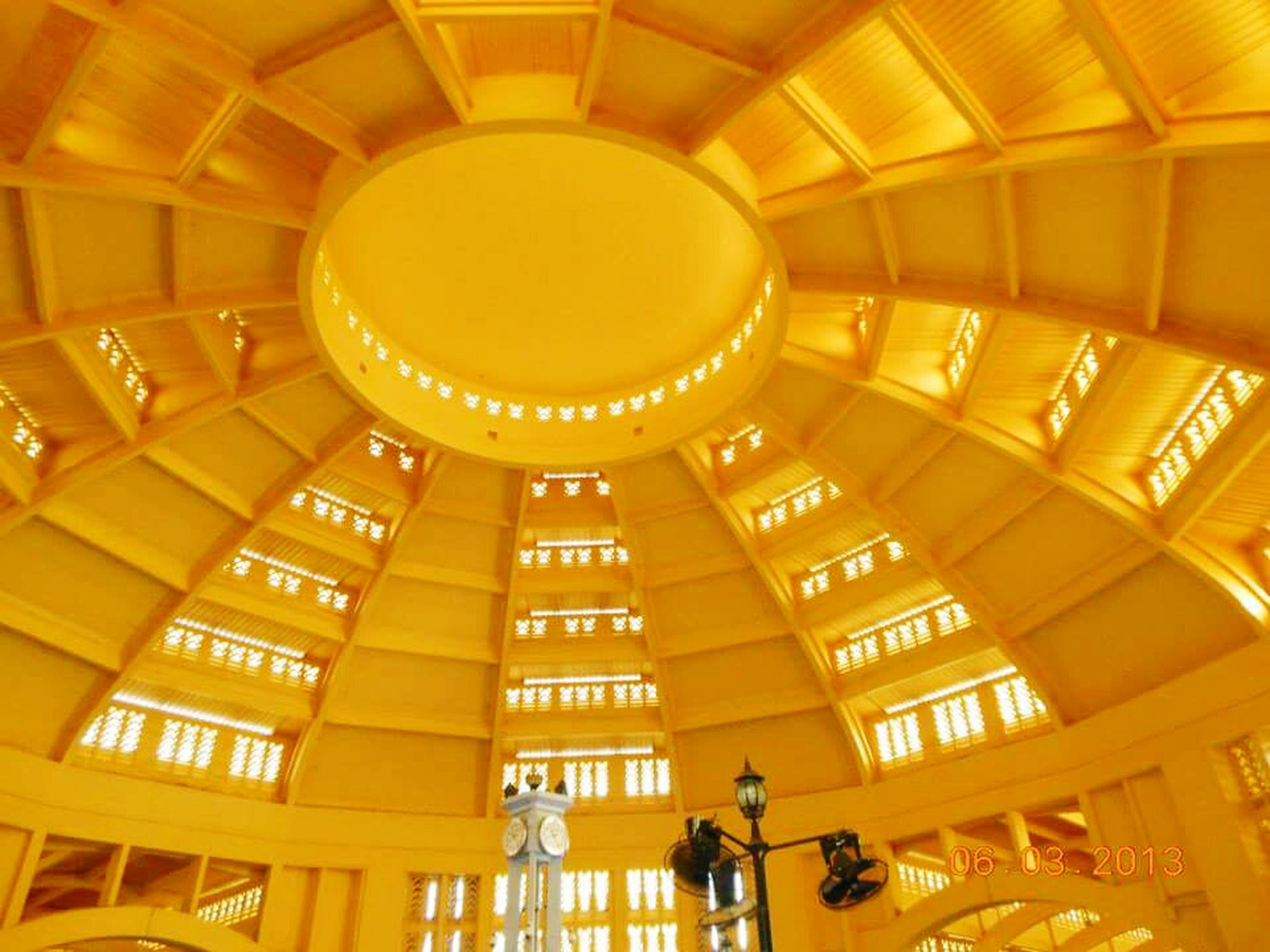 indoors, architecture, built structure, low angle view, illuminated, ceiling, modern, building, architectural feature, lighting equipment, building exterior, yellow, interior, no people, pattern, glass - material, window, shopping mall, city, in a row