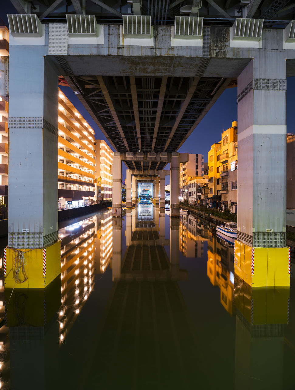 architecture, reflection, built structure, illuminated, connection, symmetry, bridge - man made structure, building exterior, no people, modern, night, indoors, city, water, sky