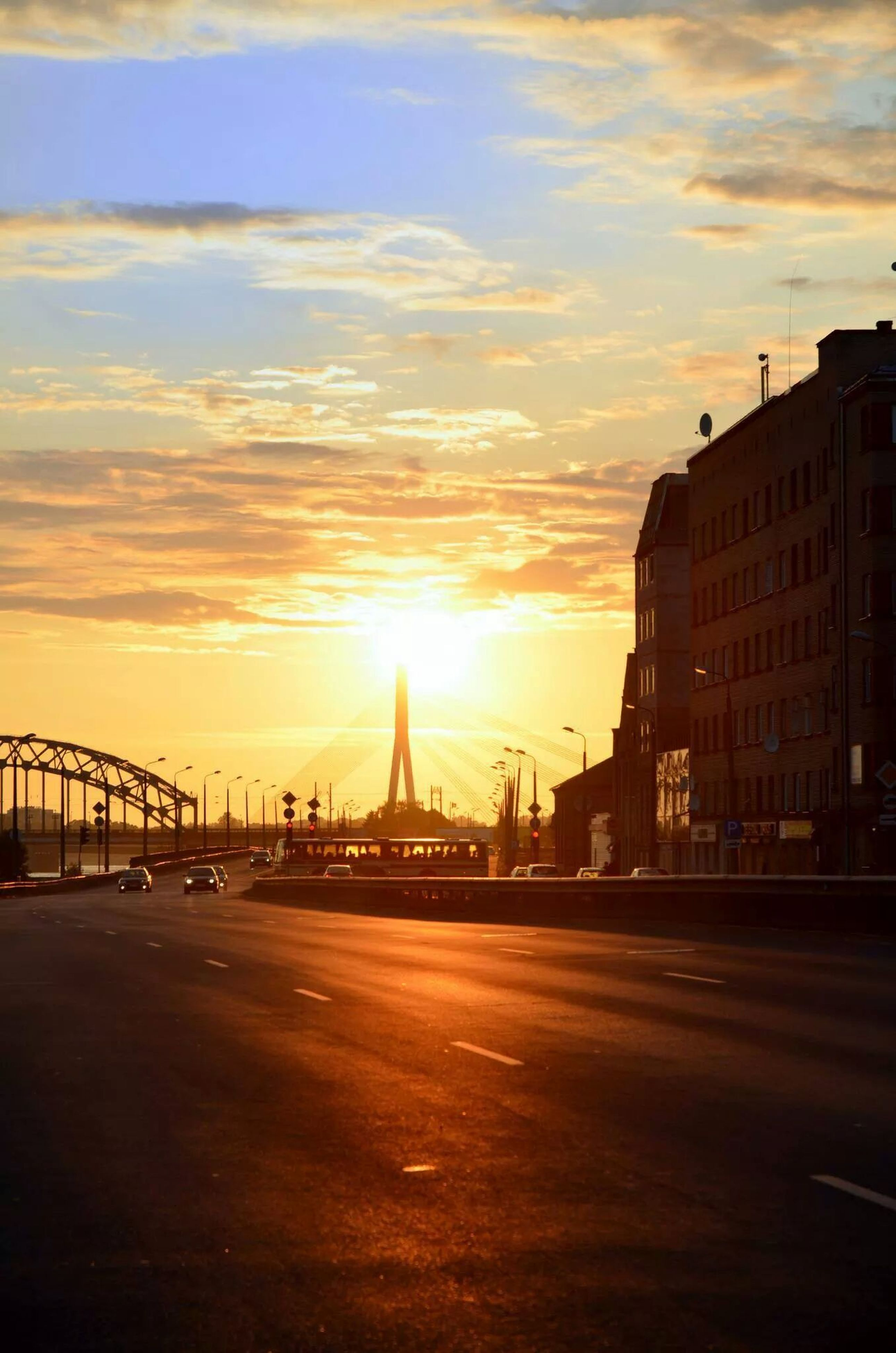 sunset, architecture, built structure, building exterior, sky, transportation, city, cloud - sky, sun, bridge - man made structure, road, orange color, connection, street, silhouette, car, the way forward, cloud, sunlight, outdoors