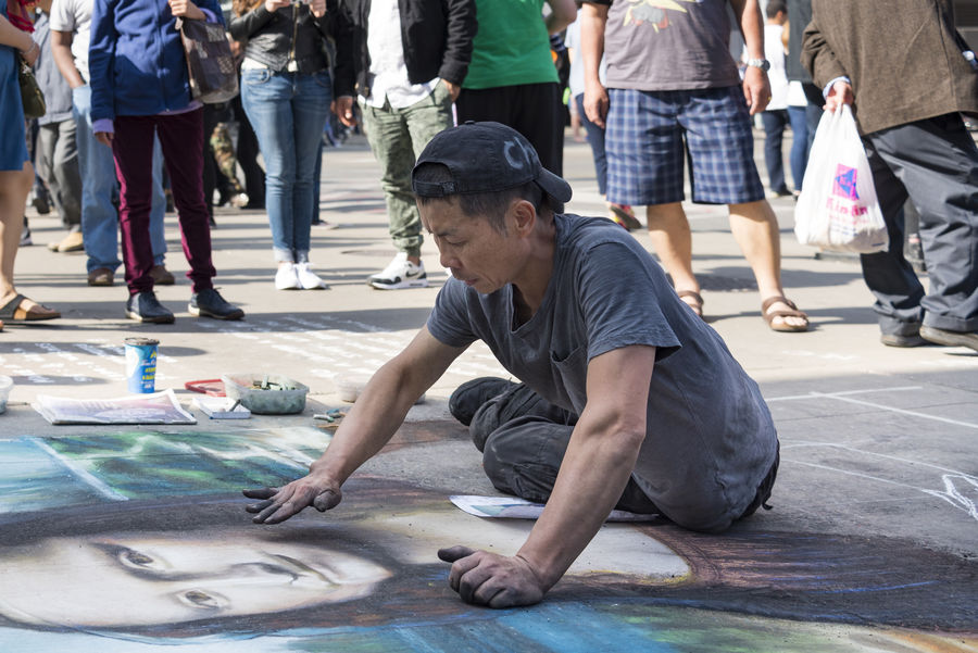 Buskering in Yonge - Dundas Square. Chinese artist Sing draws the Mona Lisa with multicolored chalks in the public urban landmark Art ArtWork Casual Clothing Chalk Chalk Art Day Drawing, Dundas Square Dundas Square Toronto Leisure Activity Lifestyle Lifestyles Mona Lisa Painting People Public Art Public Places Street Toronto Toronto Canada Urban Way Of Life Yonge-Dundas Square