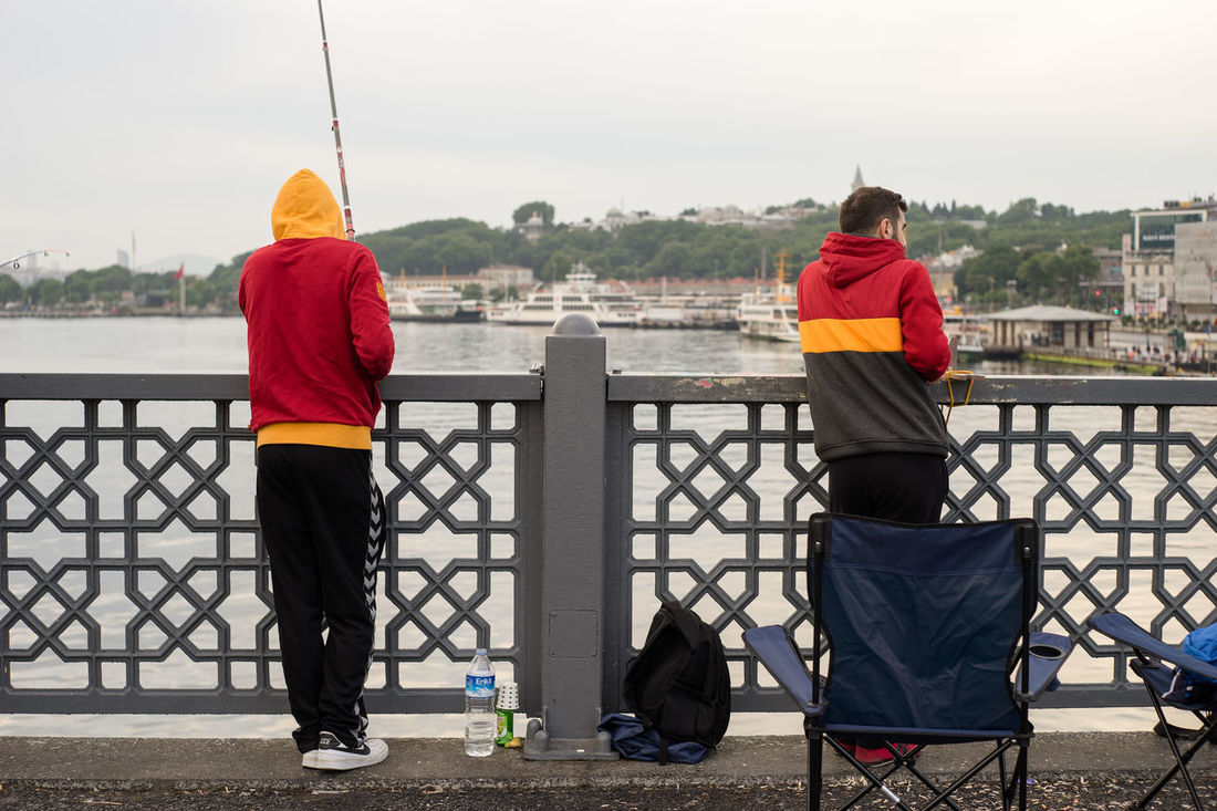 Istanbul, Turkey - Jun 28, 2015: Two men in Galatasaray football club's jacket were fishing on Galata Bridge in cool early morning, with a bag and a chair around. Bag Bosphorus Chair Cold Culture Fashion Fish Fishing Rods Football Club Football Clubs Galata Bridge GalataSaray Hobby Istanbul Jacket Lifestyle Morning People Portable Sea Sky Strait Travel Turkey Two Persons