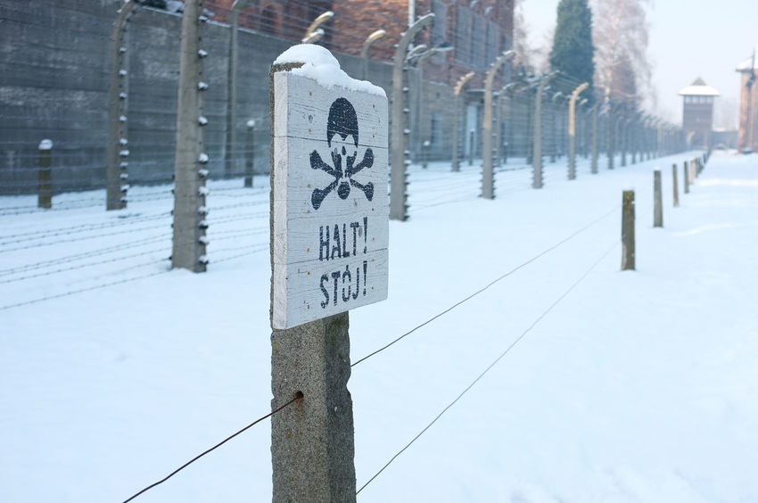 Halt sign at Auschwitz concentration camp in snow Auschwitz  Halt Sign Cold Temperature Communication Concentration Camp Fence Guidance No People Outdoors Skull And Crossbones Snow Text Winter