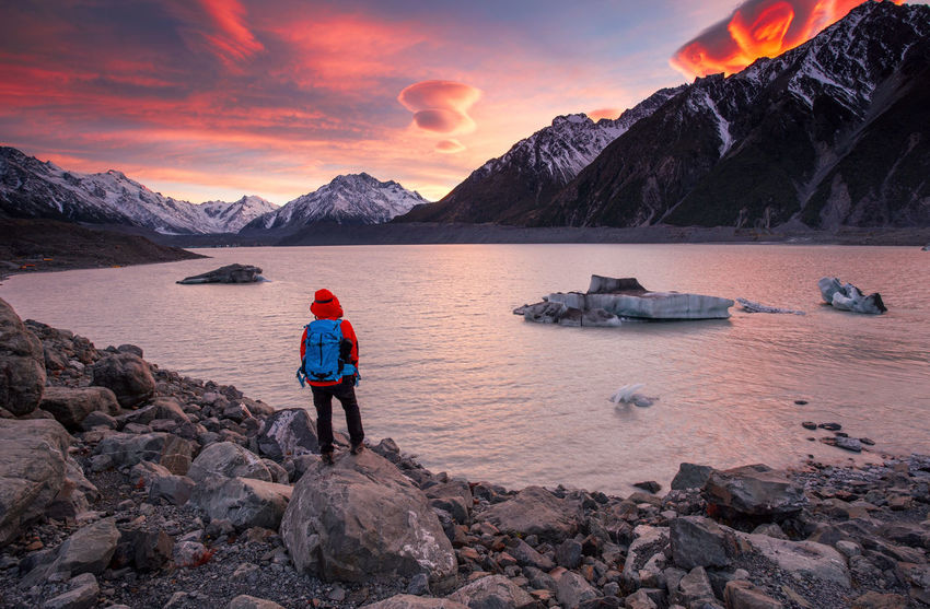 A Traveller Enjoying Beautiful Sunrise over Mount Cook, New Zealand Adventure Adventurer Backpacking Beauty In Nature Escapism Famous Place Getting Away From It All Lenticular Mount Cook New Zealand Ocean Outdoor Photography Outdoors Perspective Recreational Pursuit Scenics Shore Southern Alps Tranquil Scene Tranquility Travel Destinations Traveller Vacations Weekend Activities Wide Angle