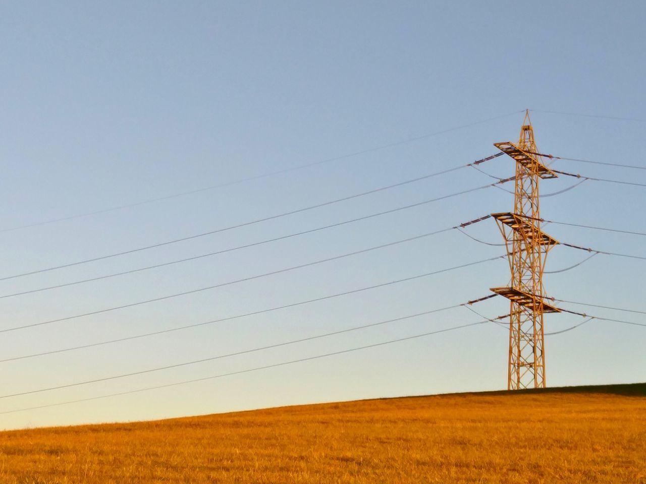 Electricity Pylon On Landscape Against Clear Sky