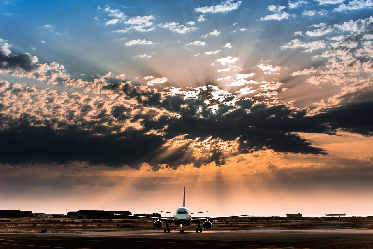 View Of Airplane On Airport Runway Against Scenic Sky