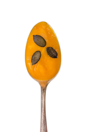 Orange pumpkin soup with seeds on a spoon Pumpkin Soup Spoon Close-up Day Food Food And Drink Freshness Fruit Healthy Eating No People Pumpkin Pumpkin Seeds Soup Studio Shot Sweet Food Vertical Format White Background White Isolated Yellow