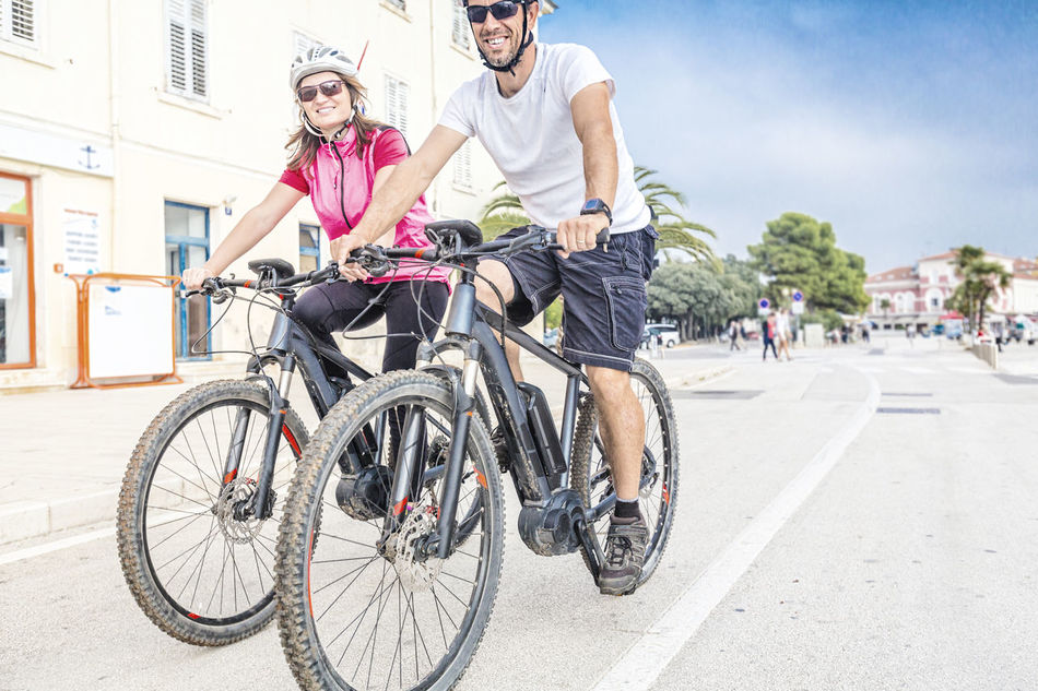 Young couple riding an E-Mountainbike in holidays Activity Bicycle Casual Clothing Couple Croatia Cycling E-bike E-montain Ebike Electric Bike France Healthy Lifestyle Holiday Italy Leisure Activity Lifestyles Mountainbike Outdoors Porec Riding Rovinj SPAIN Summer Togetherness Vacation