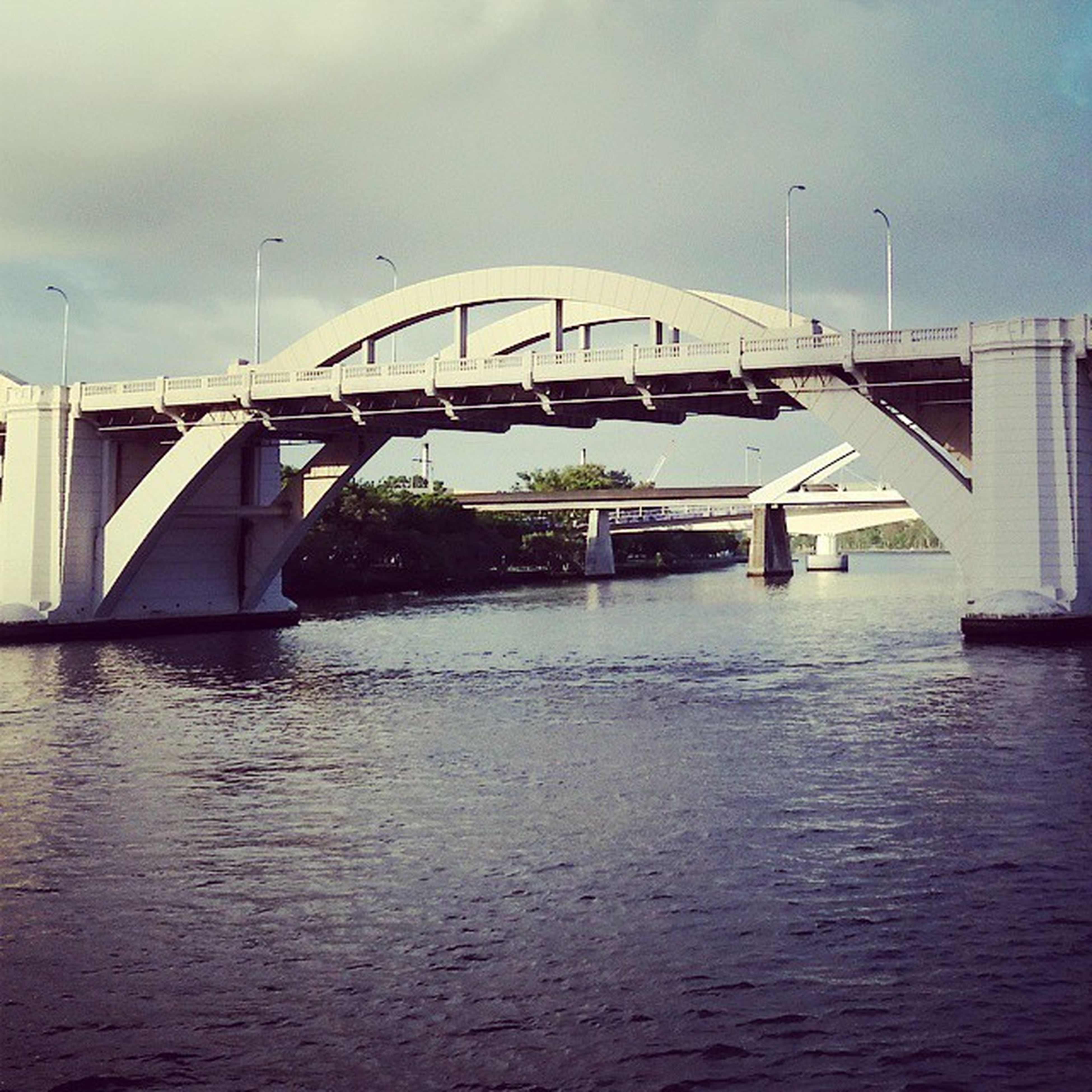 waterfront, water, built structure, architecture, sky, connection, bridge - man made structure, river, cloud - sky, transportation, bridge, building exterior, reflection, rippled, cloud, no people, nature, outdoors, day, cloudy