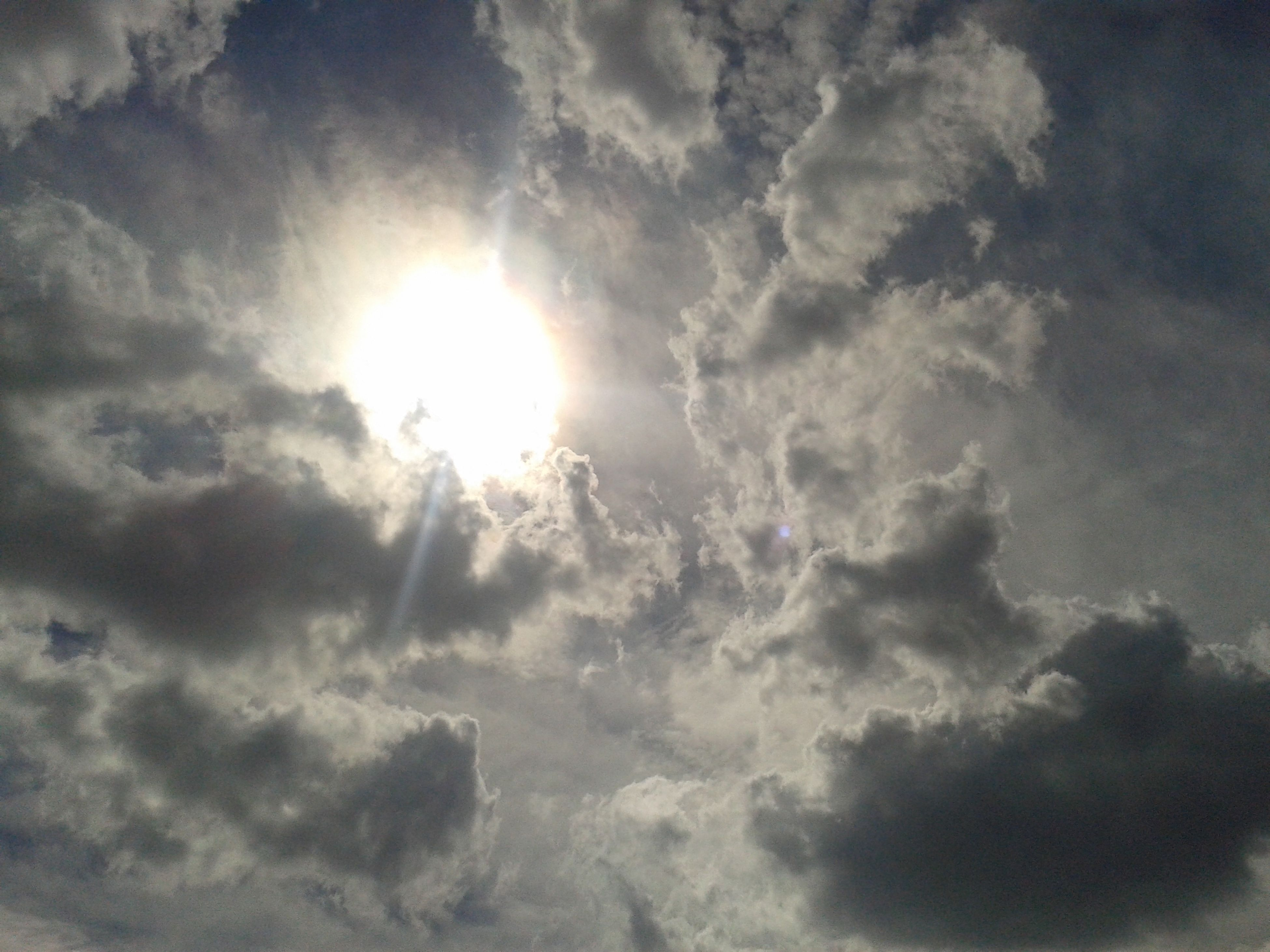 sky, cloud - sky, sun, cloudy, low angle view, sunbeam, beauty in nature, tranquility, weather, nature, scenics, tranquil scene, sunlight, cloud, cloudscape, sky only, lens flare, idyllic, outdoors, overcast