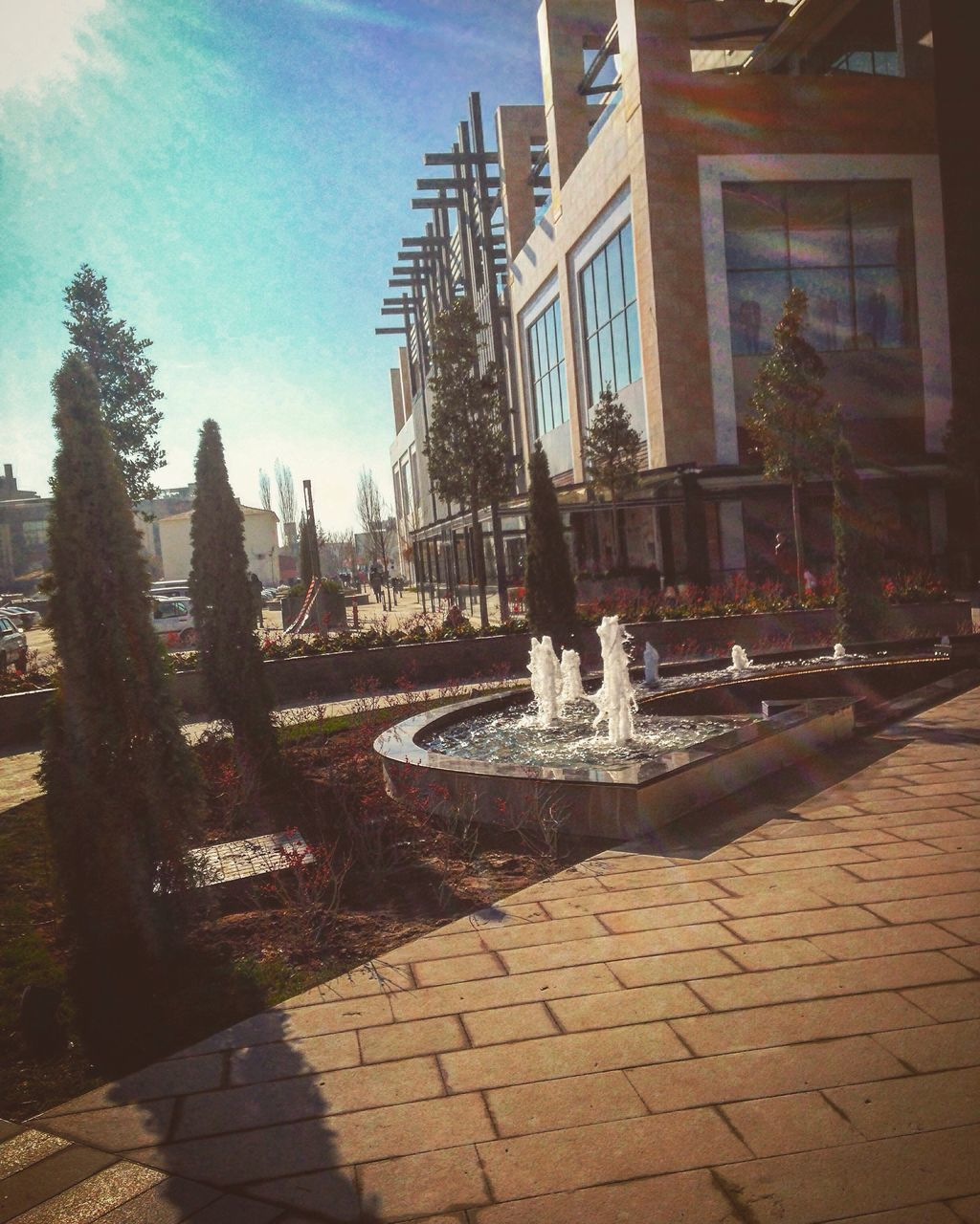 fountain, architecture, building exterior, tree, built structure, day, water, statue, motion, no people, outdoors, growth, sculpture, nature, city, sky