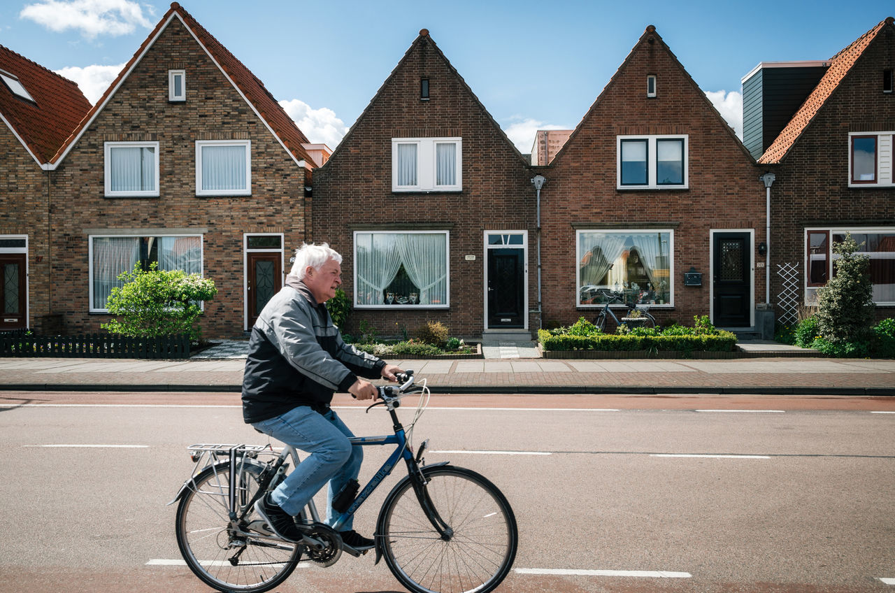 Resident of the village of Volendam by bike in front of the typical traditional houses of a Dutch fishing village, Netherlands. Adult Architecture Bicycle Building Exterior Built Structure Casual Clothing Cycling Day House Lifestyles Mode Of Transport One Man Only One Person Outdoors Real People Residential Building Senior Adult Street Transportation