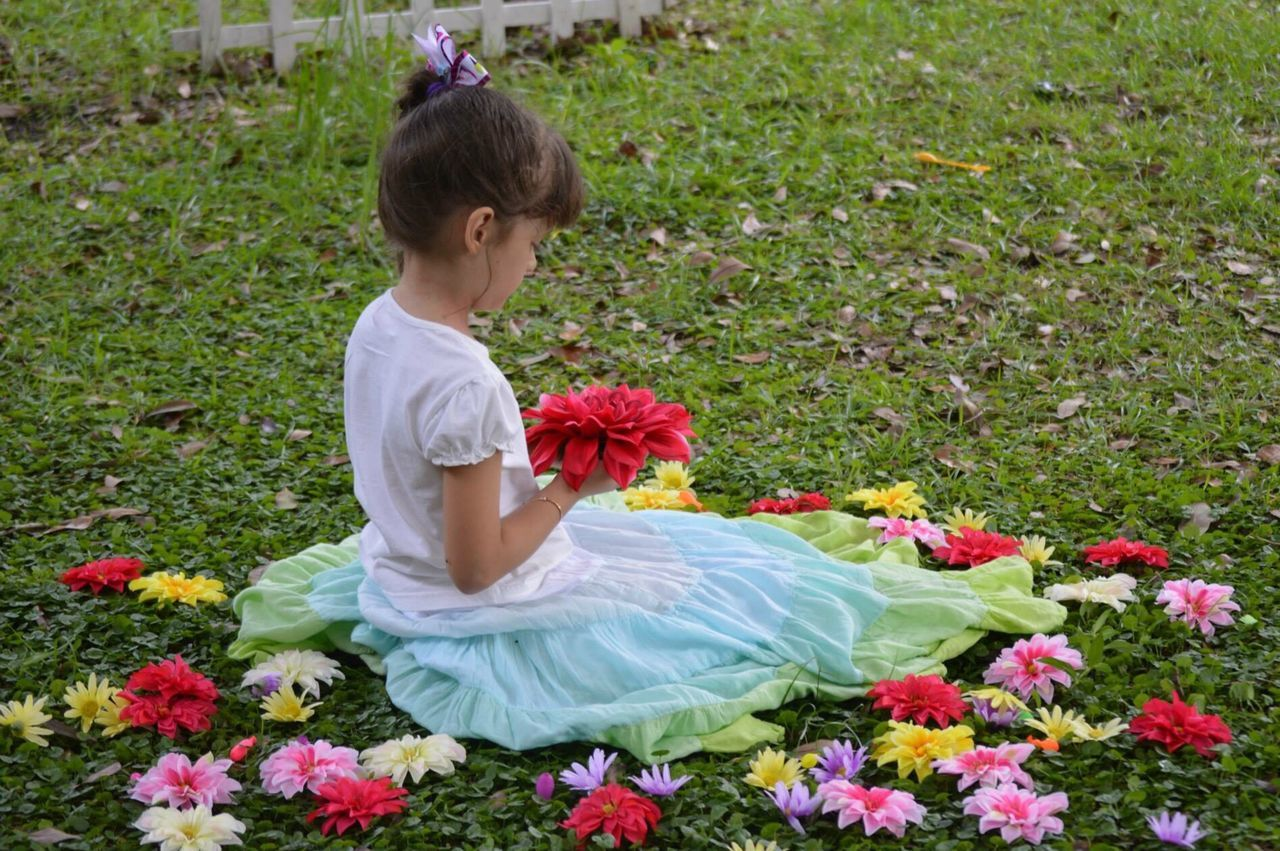Full Length Of Girl Wearing Dress With Flowers Sitting On Grassy Field