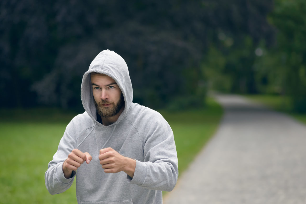 Young man working out in a park punching air Athlete Athletic Beard Bearded Concentrated Face Fit Fitness Focused Jogging Male Man Outdoors Park Portrait Punching Running Shadow Boxing Sport Young