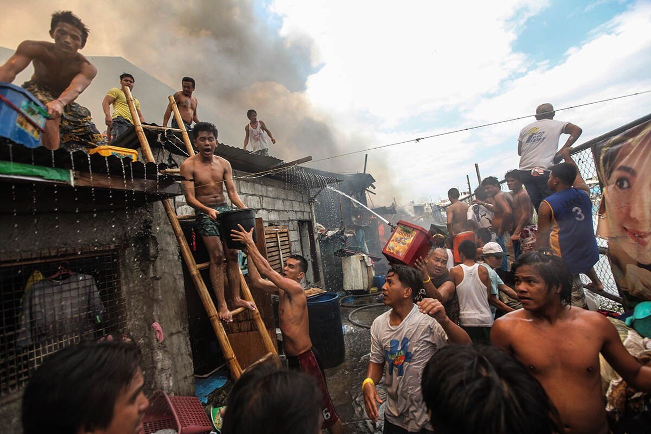 The Photojournalist - 2017 EyeEm Awards People help each other extinguish the fire that engulf houses in Manila, Philippines. The Human Condition