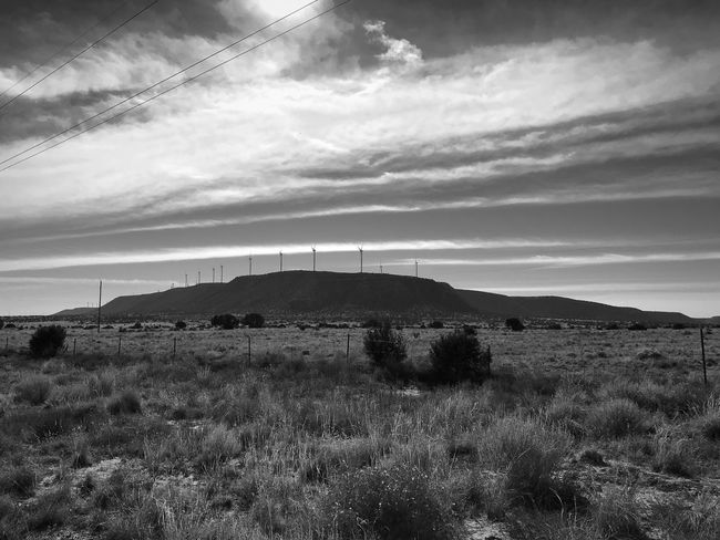 """""""King's Of The Mountain"""" A windmill power farm atop a high plateau that rises above the grasslands of Central New Mexico. Plateau New Mexico Skies New Mexico Photography Windmill Farm Windmills Grasslands Blackandwhite Photography Black & White Blackandwhite Sky Grass Field Landscape Nature No People Cloud - Sky Scenics"""