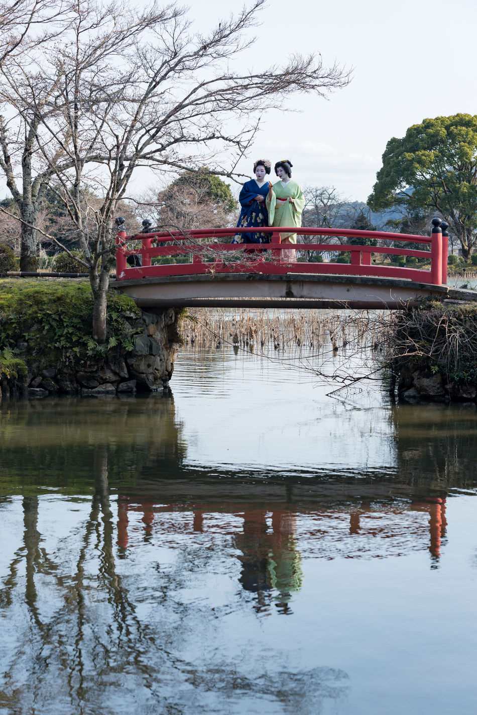 Two geishas on a red bridge with water reflection - Kyoto Branch Bridge - Man Made Structure Connection Day Footbridge Full Length Geisha Japan Japan Photography Japanese Culture Japanese Style Kyoto Men Nature Outdoors People Real People Reflection River Sky Standing Togetherness Tree Water Women