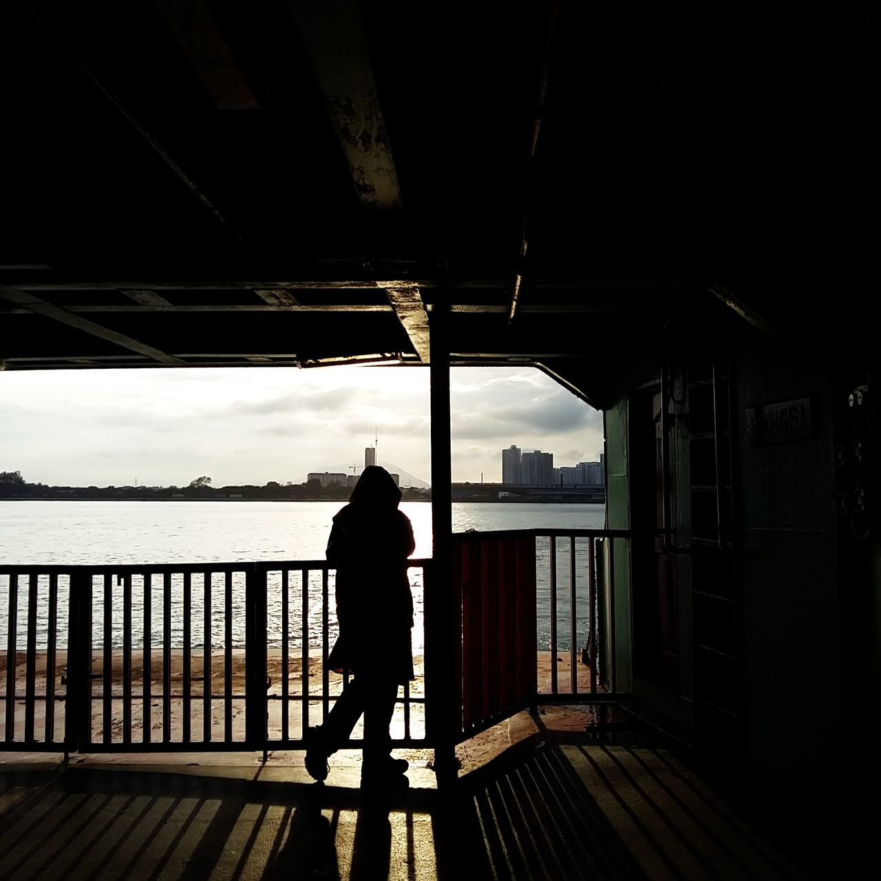 Full Length Of Silhouette Person Walking At Corridor By River