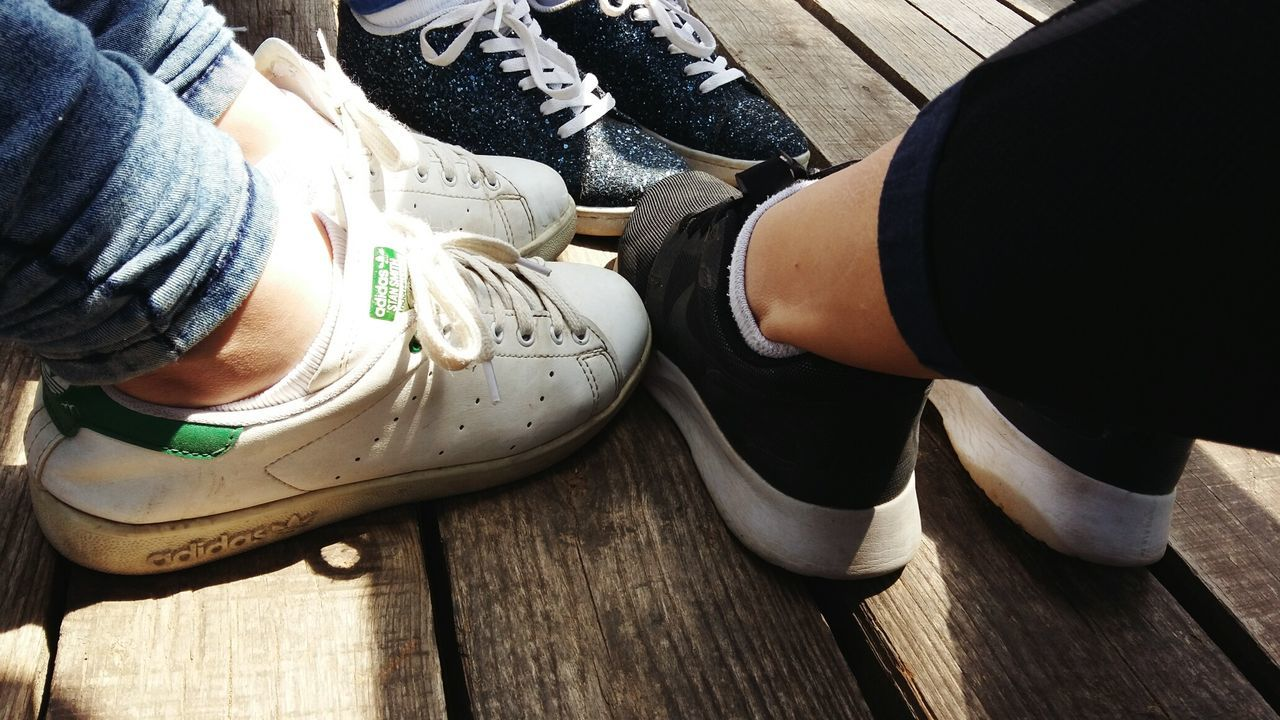 shoe, real people, high angle view, human body part, human hand, one person, low section, human leg, wood - material, day, men, leisure activity, sitting, lifestyles, indoors, close-up, people