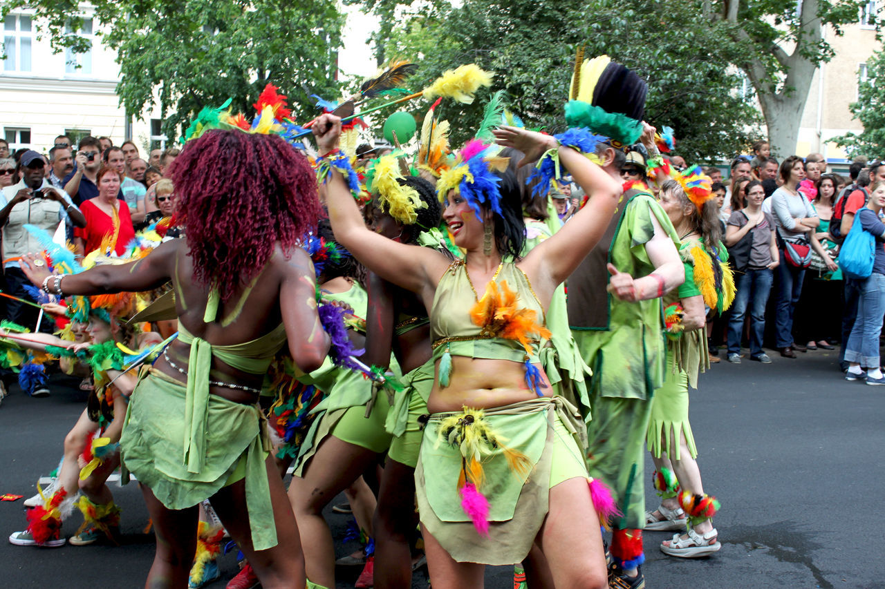 a woman posing with her dancing group at the carnival of cultures Berlin Carnival Colors Cultures Dance Dancing Enjoyment Feathers Federn Freude Friendship Front View Fun Färben Karneval Der Kulturen Lifestyles Posing Real People Smiling Tanzen Togetherness Tänzerin Women Young Adult Young Women