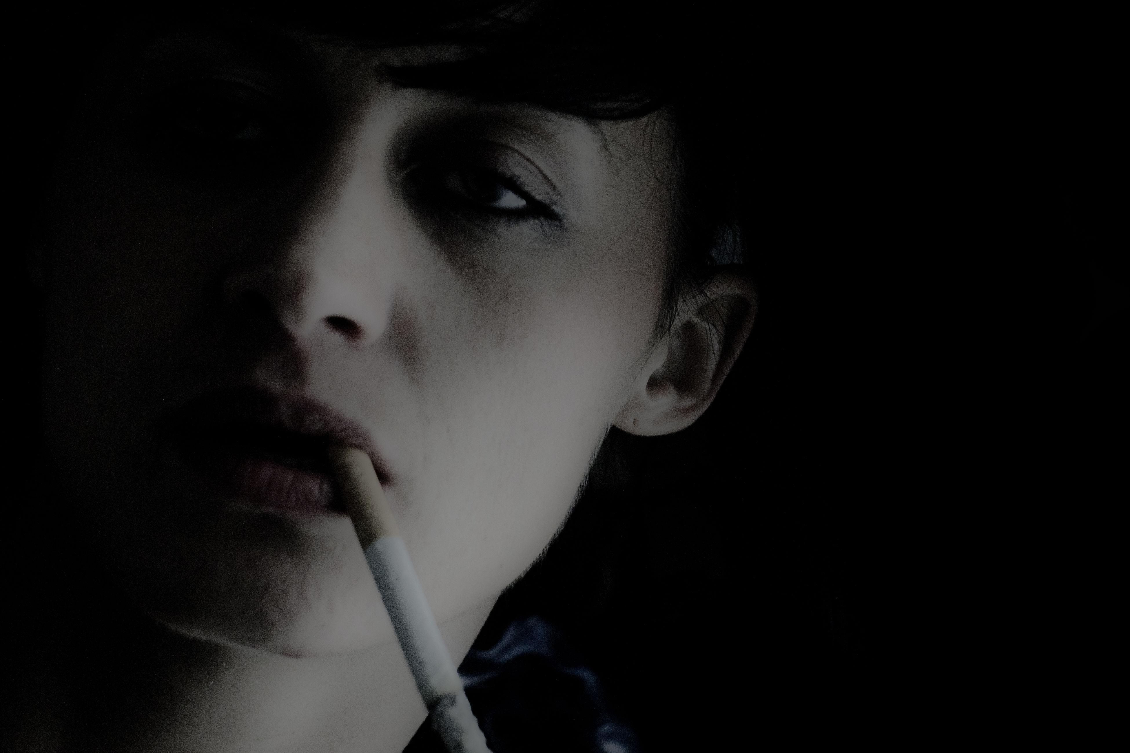 headshot, lifestyles, close-up, portrait, human face, contemplation, serious, leisure activity, black background, staring