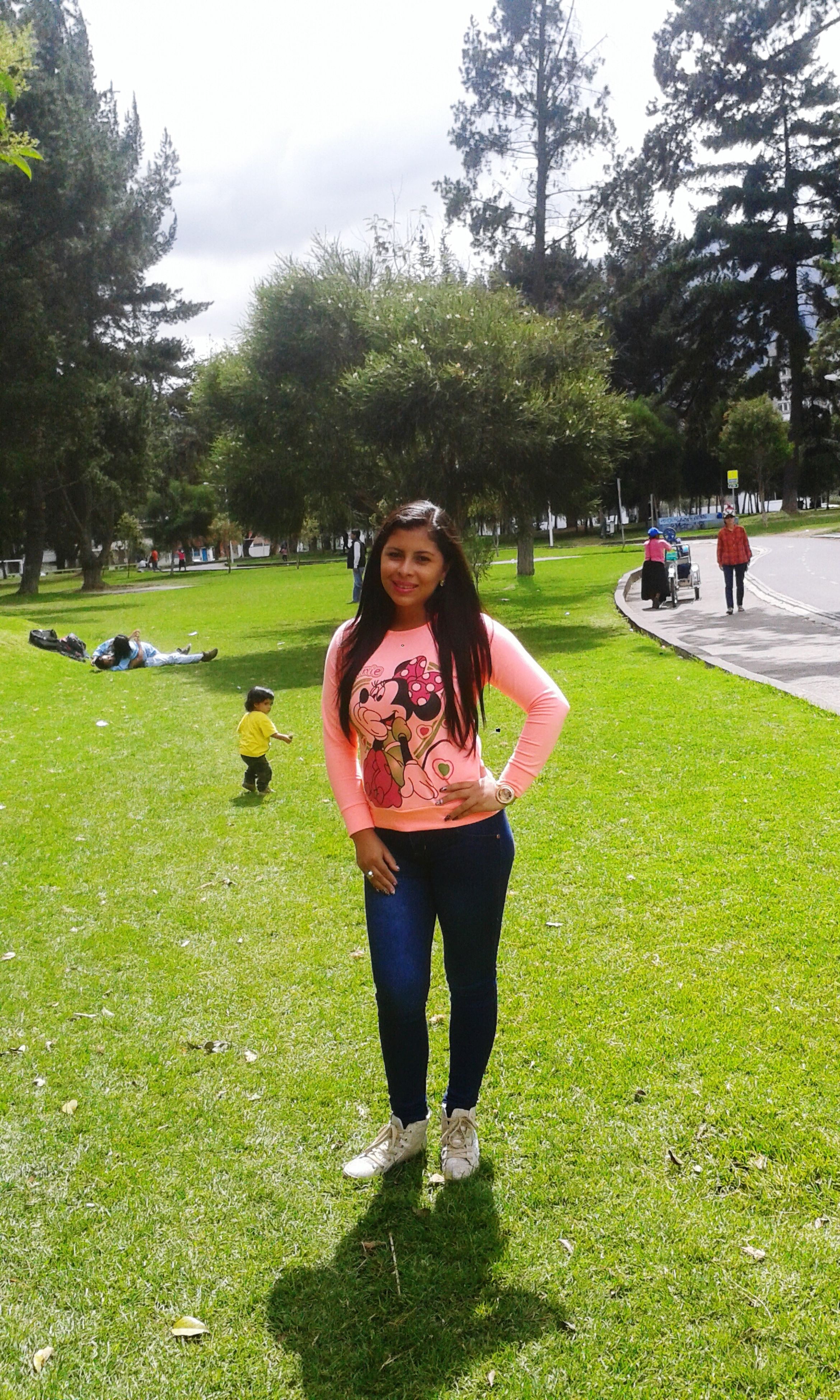 lifestyles, leisure activity, tree, grass, casual clothing, park - man made space, person, full length, young women, young adult, looking at camera, front view, enjoyment, green color, park, smiling, girls, portrait