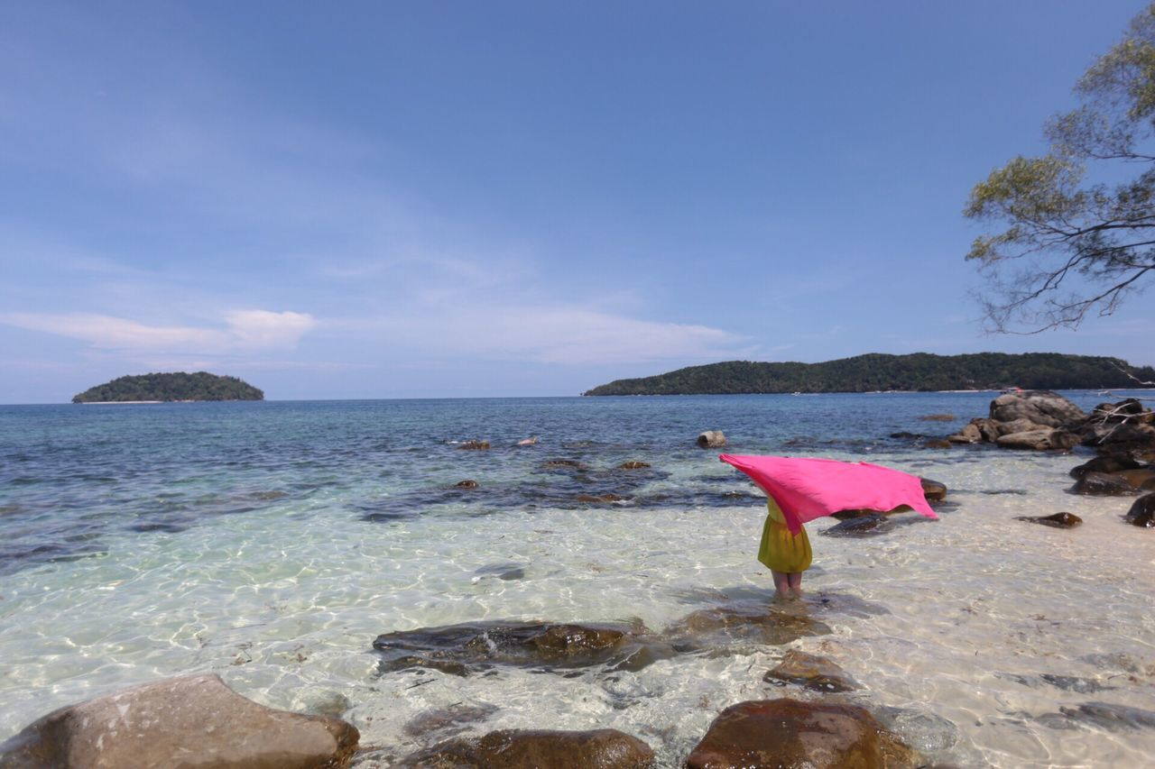 Rear View Of Woman Holding Pink Sarong In Sea Against Sky