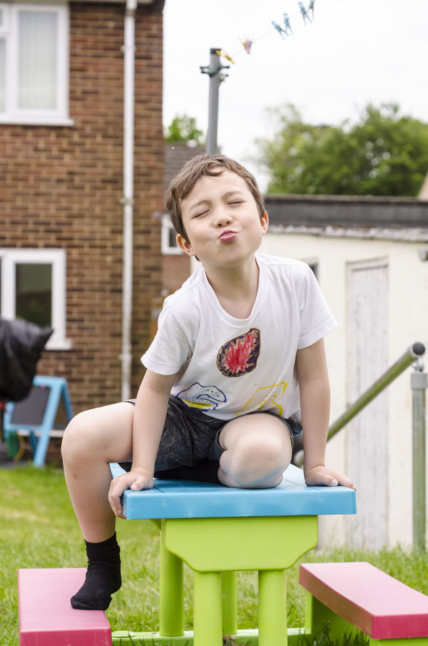 A young boy sits on a picnic table, posing and sticking his tongue out. Back Garden Boy Check This Out Childhood Cute Fun Fun Garden Happy Outdoors Outside Person Picnic Table Portrait Posing Shorts Sticking Out Tongue White T-shirt Young