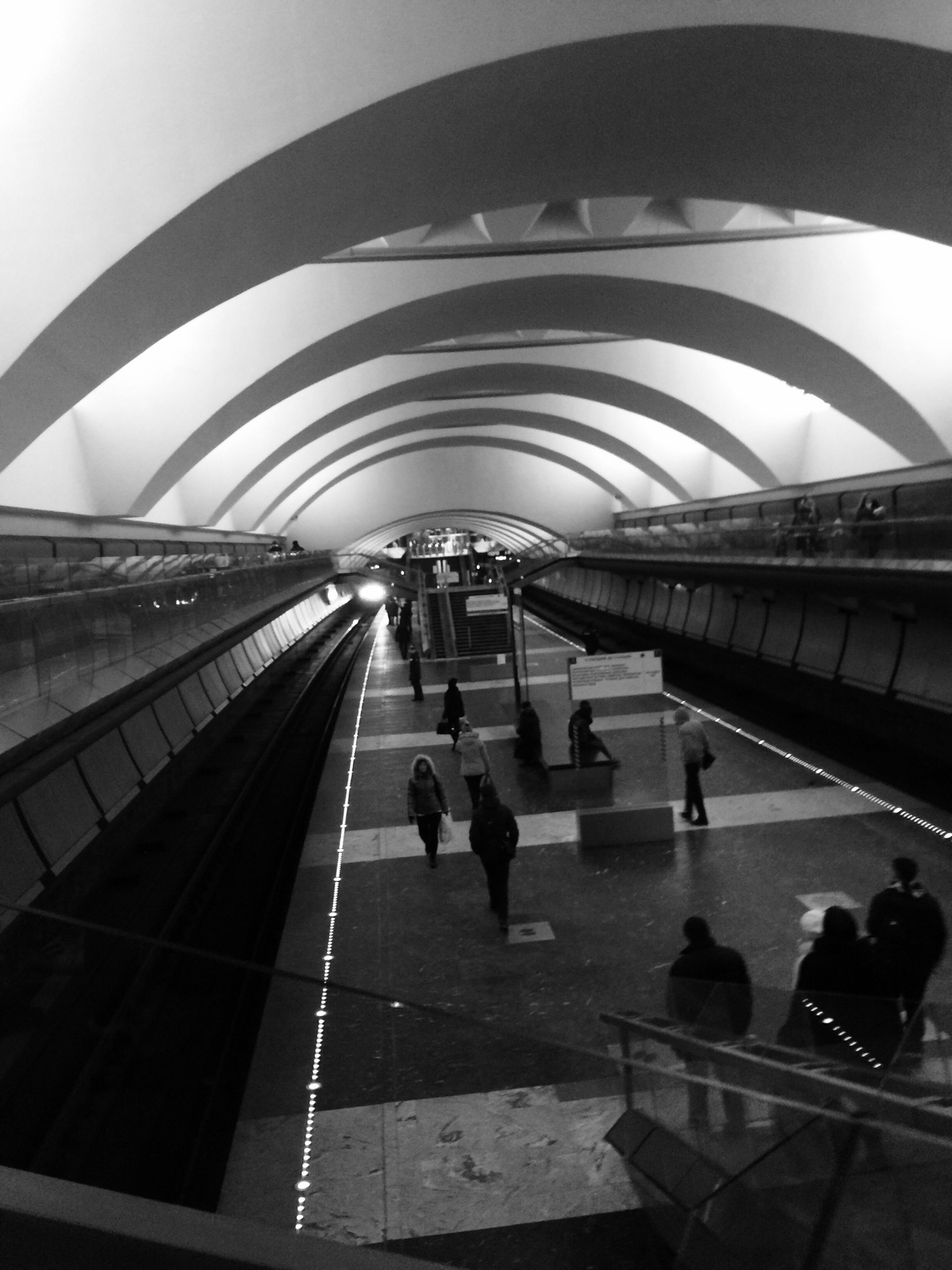 indoors, ceiling, large group of people, architecture, railroad station, built structure, travel, person, men, public transportation, transportation building - type of building, incidental people, subway station, modern, illuminated, railroad station platform, transportation, lifestyles, walking