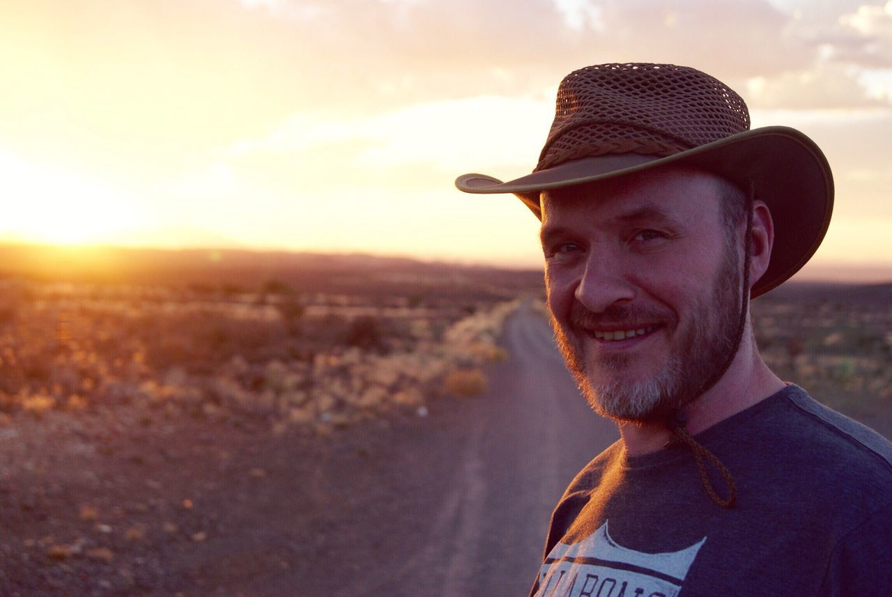 Portrait Of Smiling Mature Man Standing On Road Against Sky At Karoo During Sunset