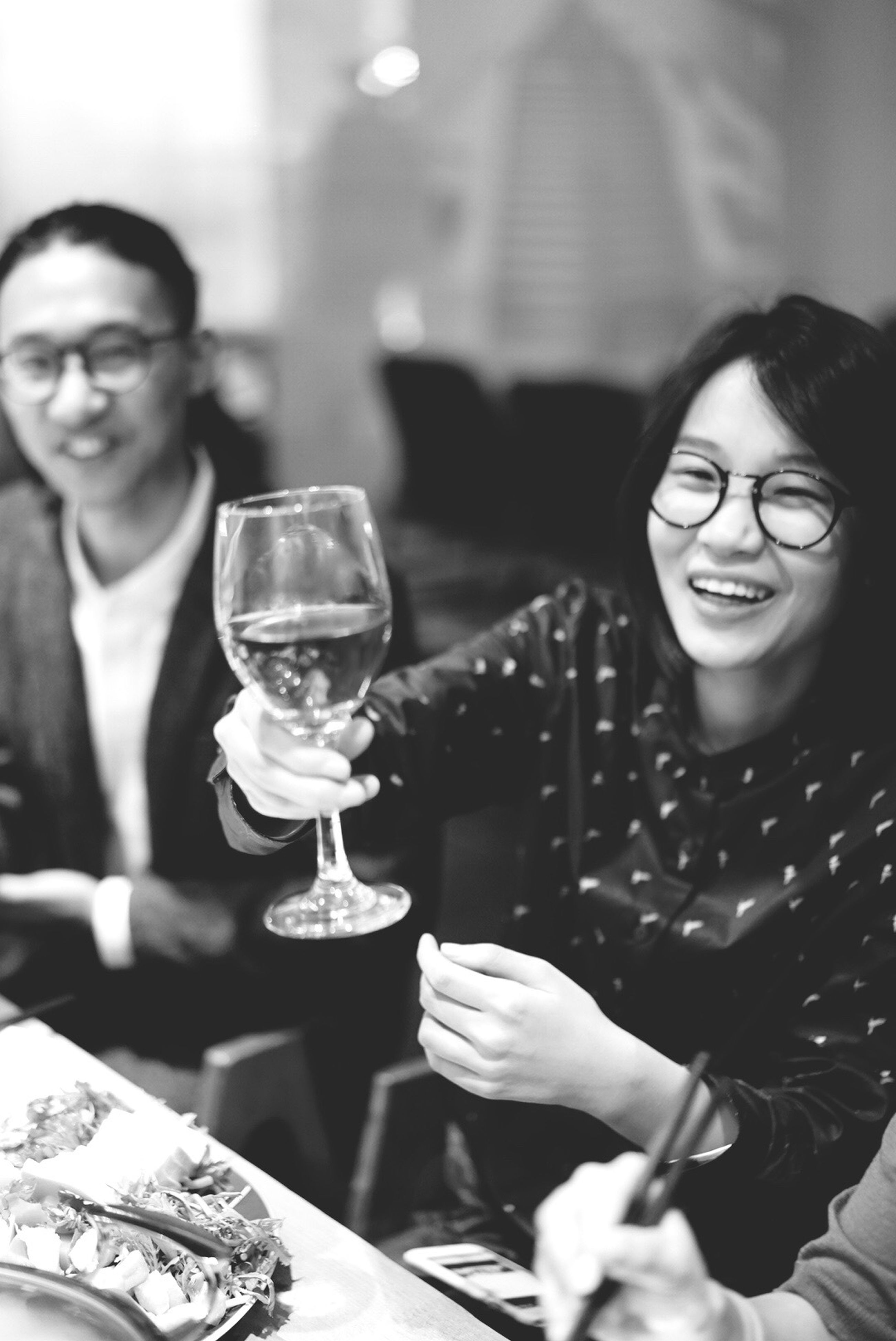 two people, smiling, wine, wineglass, sitting, togetherness, women, real people, happiness, lifestyles, focus on foreground, cheerful, holding, enjoyment, drink, drinking glass, alcohol, indoors, friendship, front view, leisure activity, table, celebratory toast, adult, men, people, bonding, young women, young adult, adults only, only women, night, happy hour