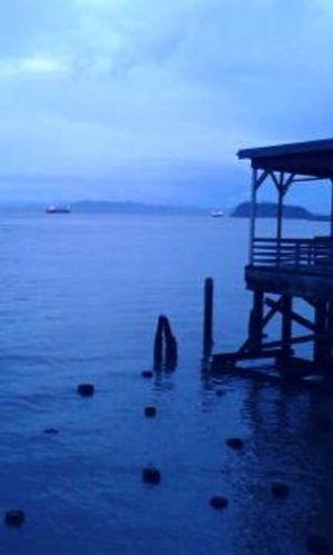 Old cannery piles lean on each other at dusk.