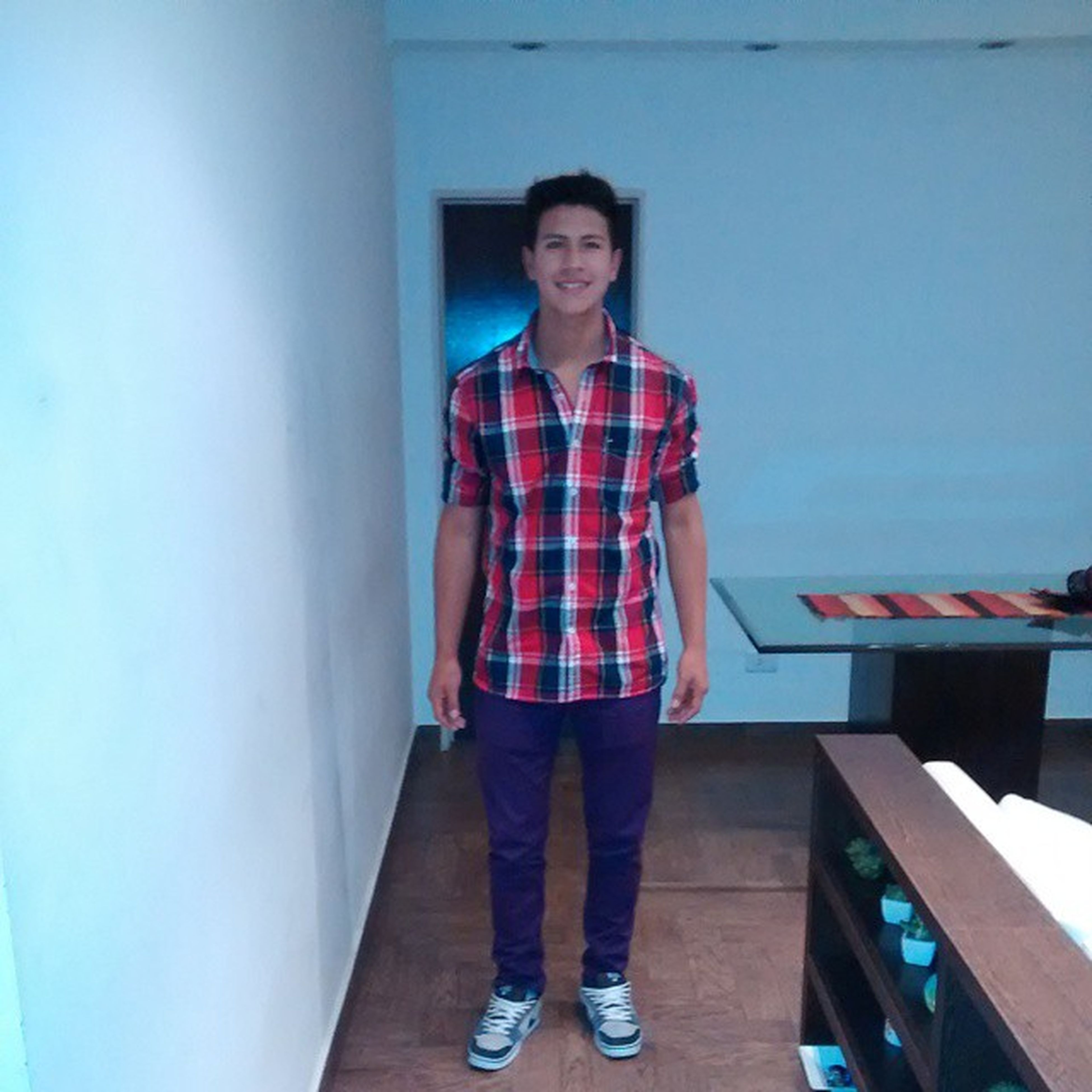 casual clothing, standing, looking at camera, portrait, front view, lifestyles, person, young adult, full length, three quarter length, leisure activity, built structure, blue, architecture, young men, indoors, smiling