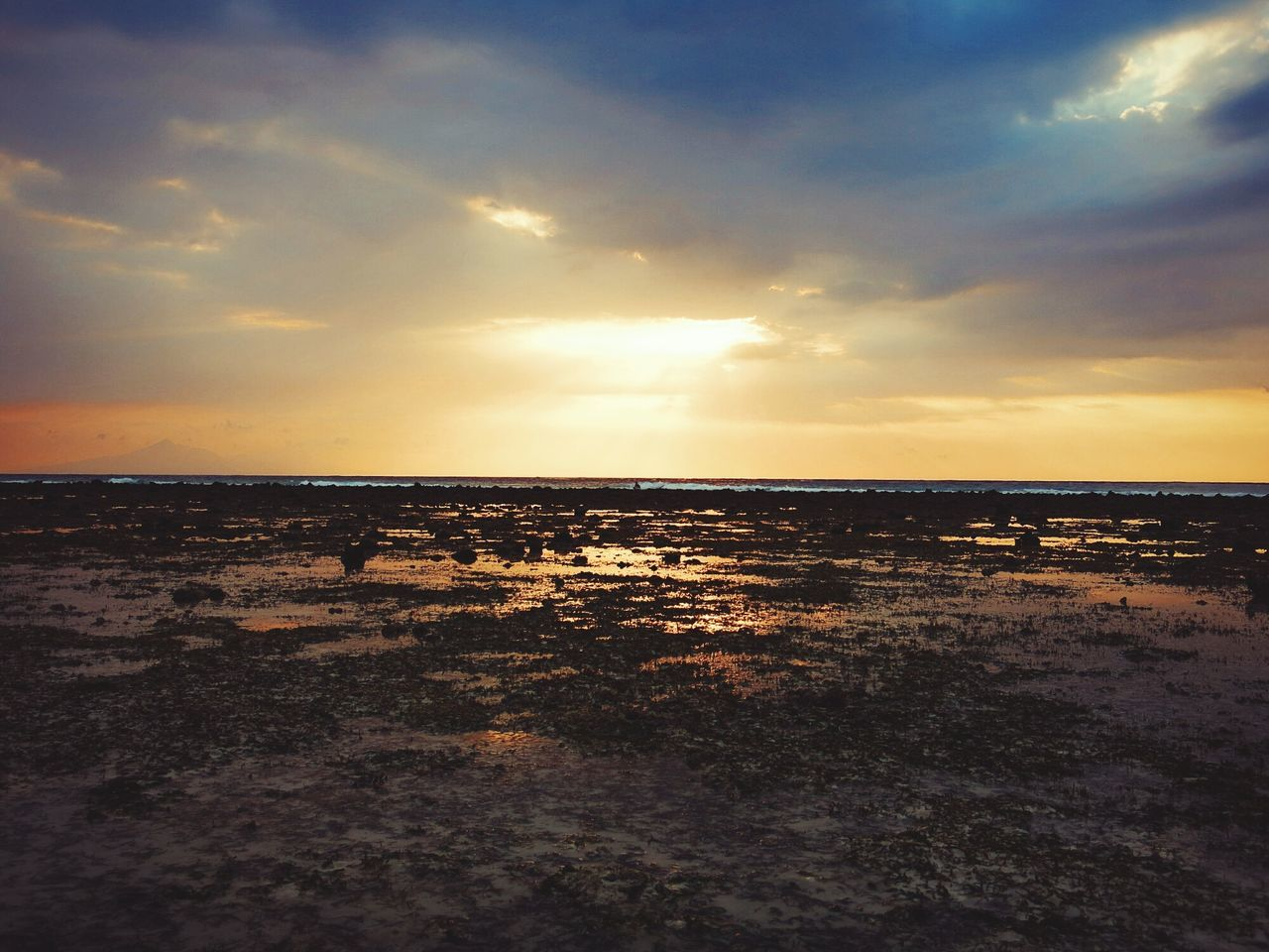 View Of Sandy Beach Against Cloudy Sky During Sunset