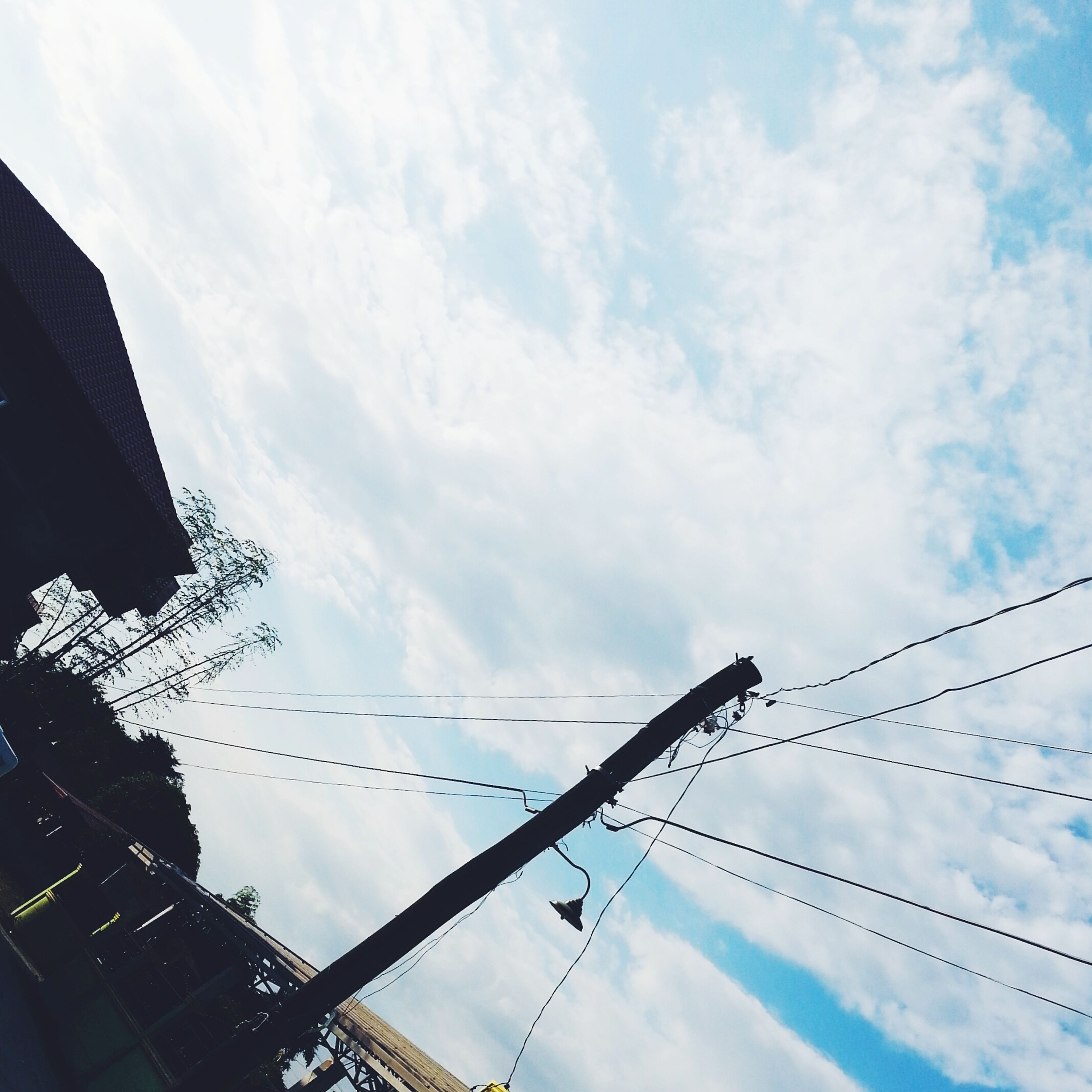 low angle view, sky, cloud - sky, built structure, architecture, building exterior, cloudy, power line, cloud, cable, connection, electricity pylon, tall - high, day, outdoors, electricity, city, no people, power supply, blue