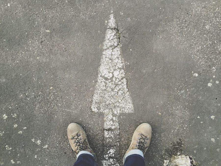 Feet Street Arrow Symbol Direction Straight Forward Low Section Personal Perspective Standing Real People One Person High Angle View Shoe Directly Above Human Leg Road Outdoors Day Asphalt Human Body Part Men
