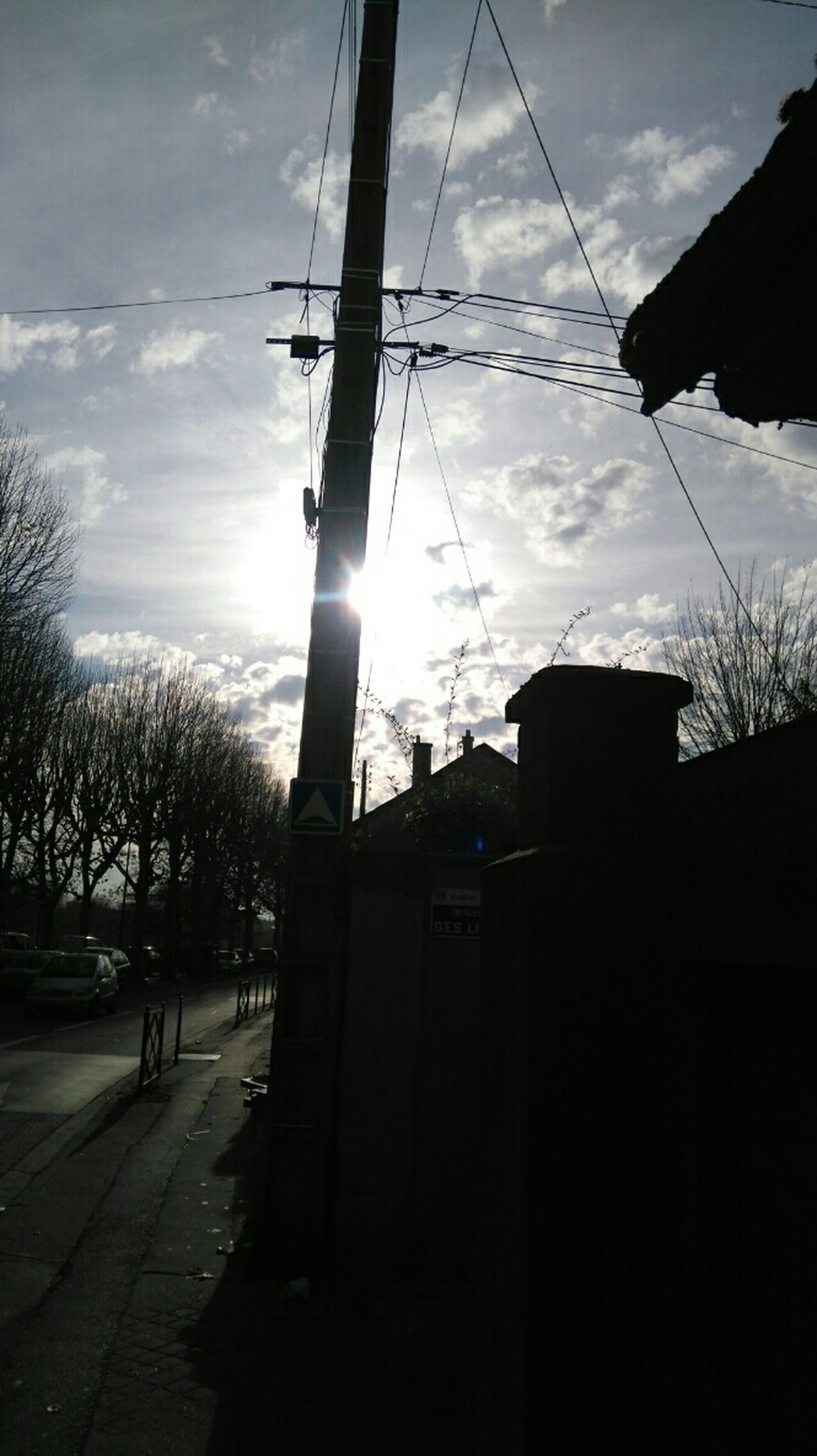 sky, silhouette, power line, electricity pylon, built structure, building exterior, architecture, electricity, cloud - sky, tree, low angle view, fuel and power generation, power supply, cloud, cable, street light, sunlight, technology, power cable, cloudy