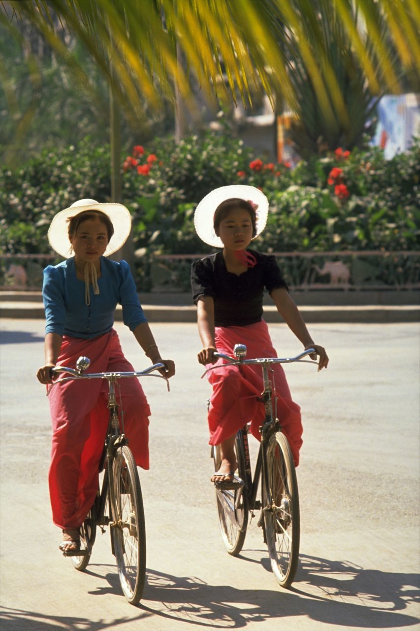 two people, bicycle, togetherness, headwear, hat, happiness, friendship, senior adult, leisure activity, cycling, outdoors, senior women, holding, riding, vacations, rural scene, adult, summer, smiling, people, motion, tree, cycling helmet, cowboy hat, adults only, day