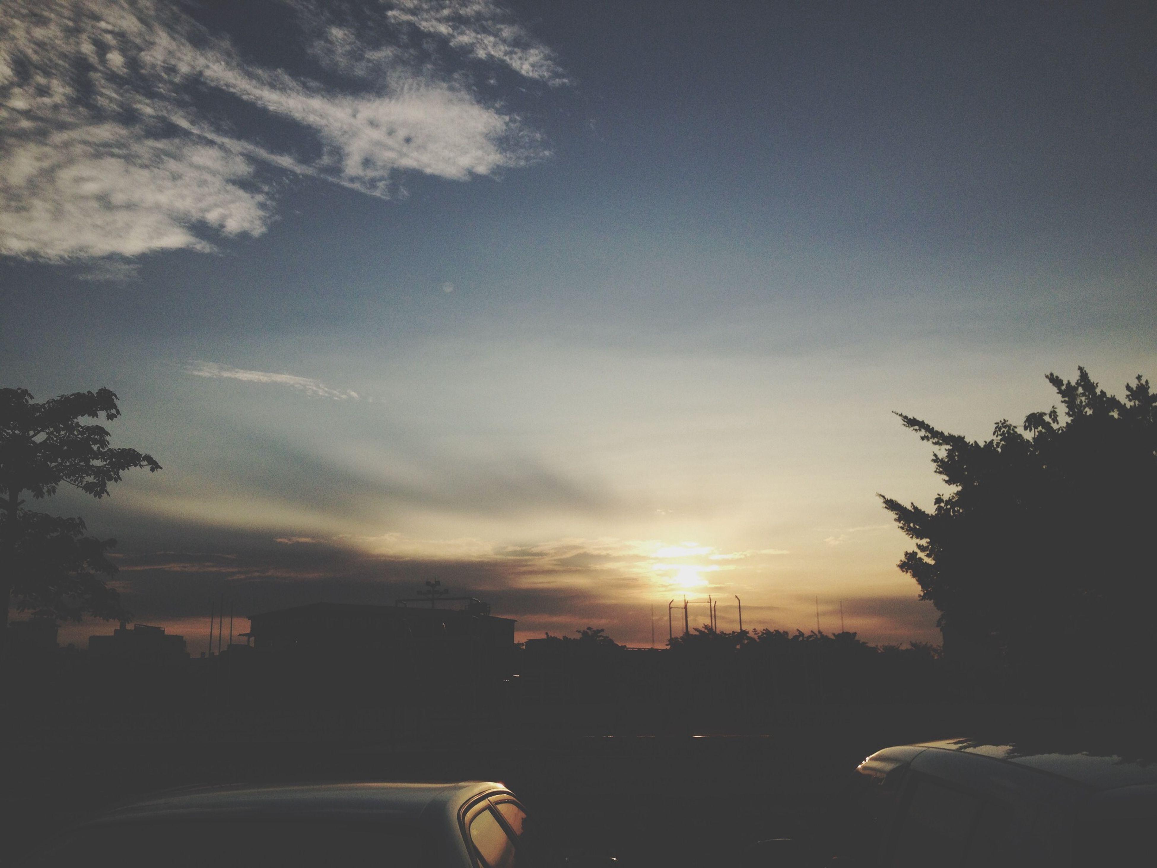 sunset, transportation, car, sky, silhouette, land vehicle, mode of transport, road, tree, sun, cloud - sky, scenics, beauty in nature, cloud, nature, tranquil scene, sunlight, orange color, tranquility, street