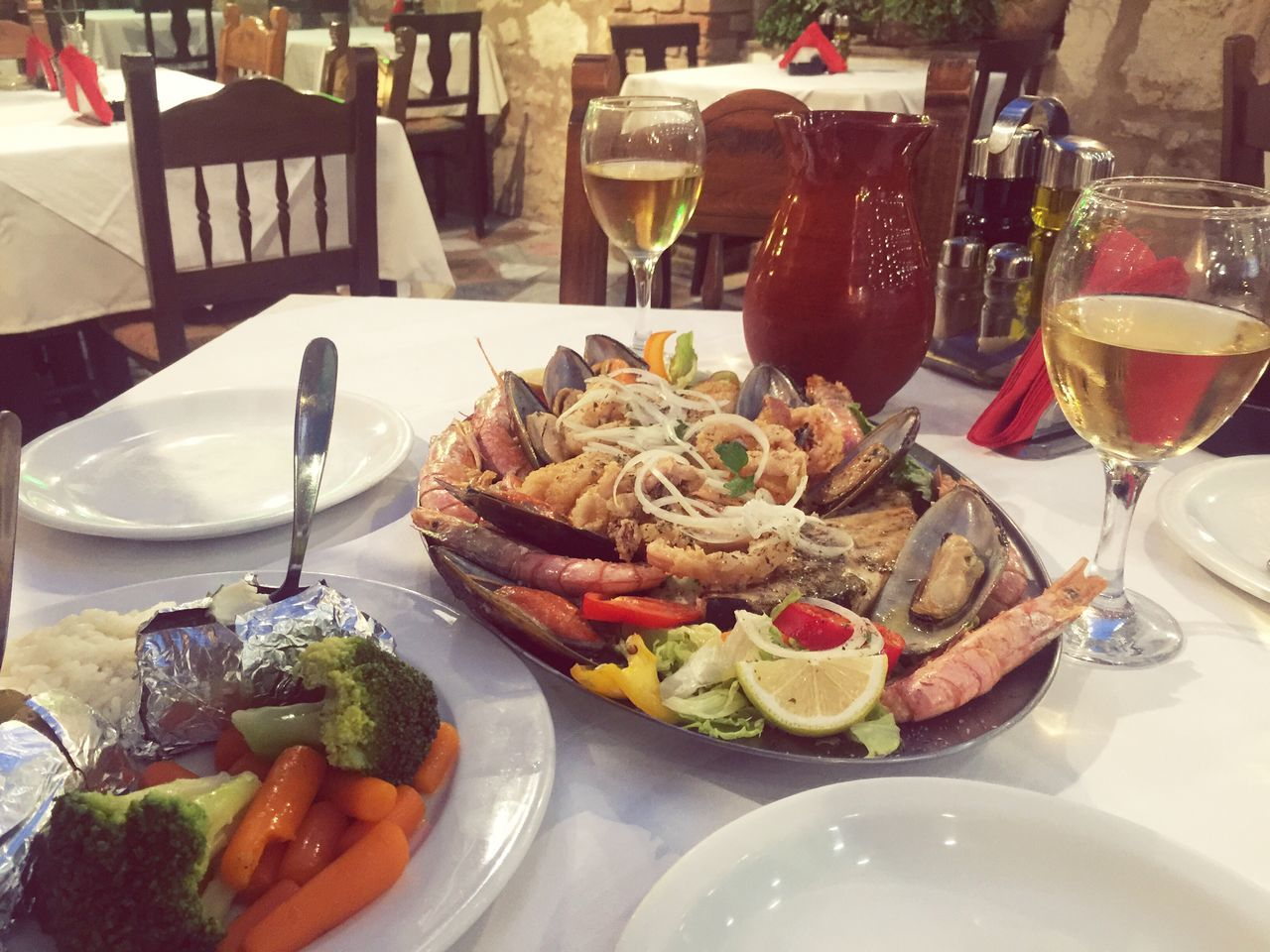 Greek dinner at a local tavern. Table Seafood Shrimps Greekfood Food Plate Wineglass Ready-to-eat Freshness Wine Meal Meat Drinking Glass Close-up Drink Serving Size Prepared Potato Healthy Eating Outdoors No People Fast Food Day