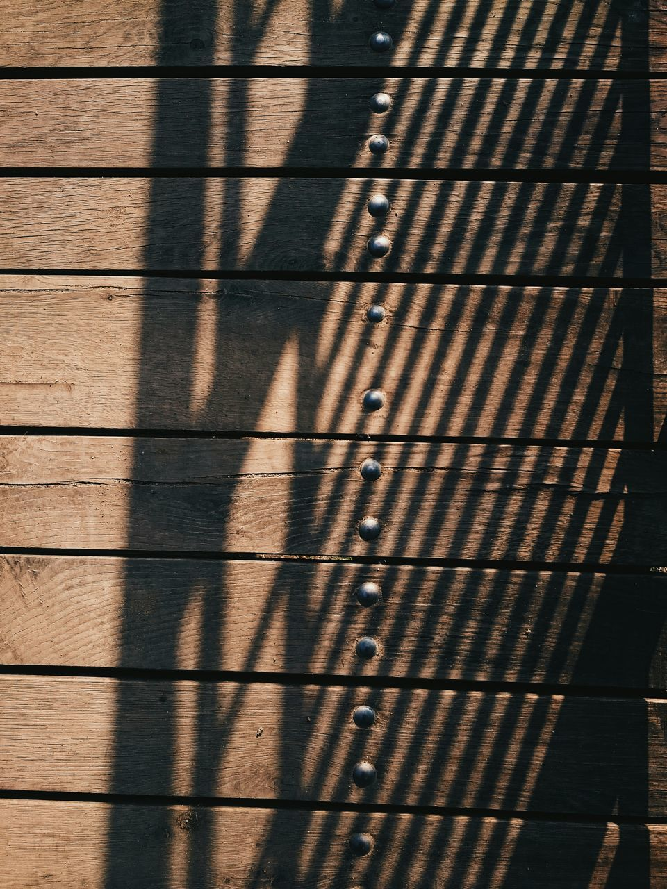 Close-Up Of Wooden Plank Wall With Shadow