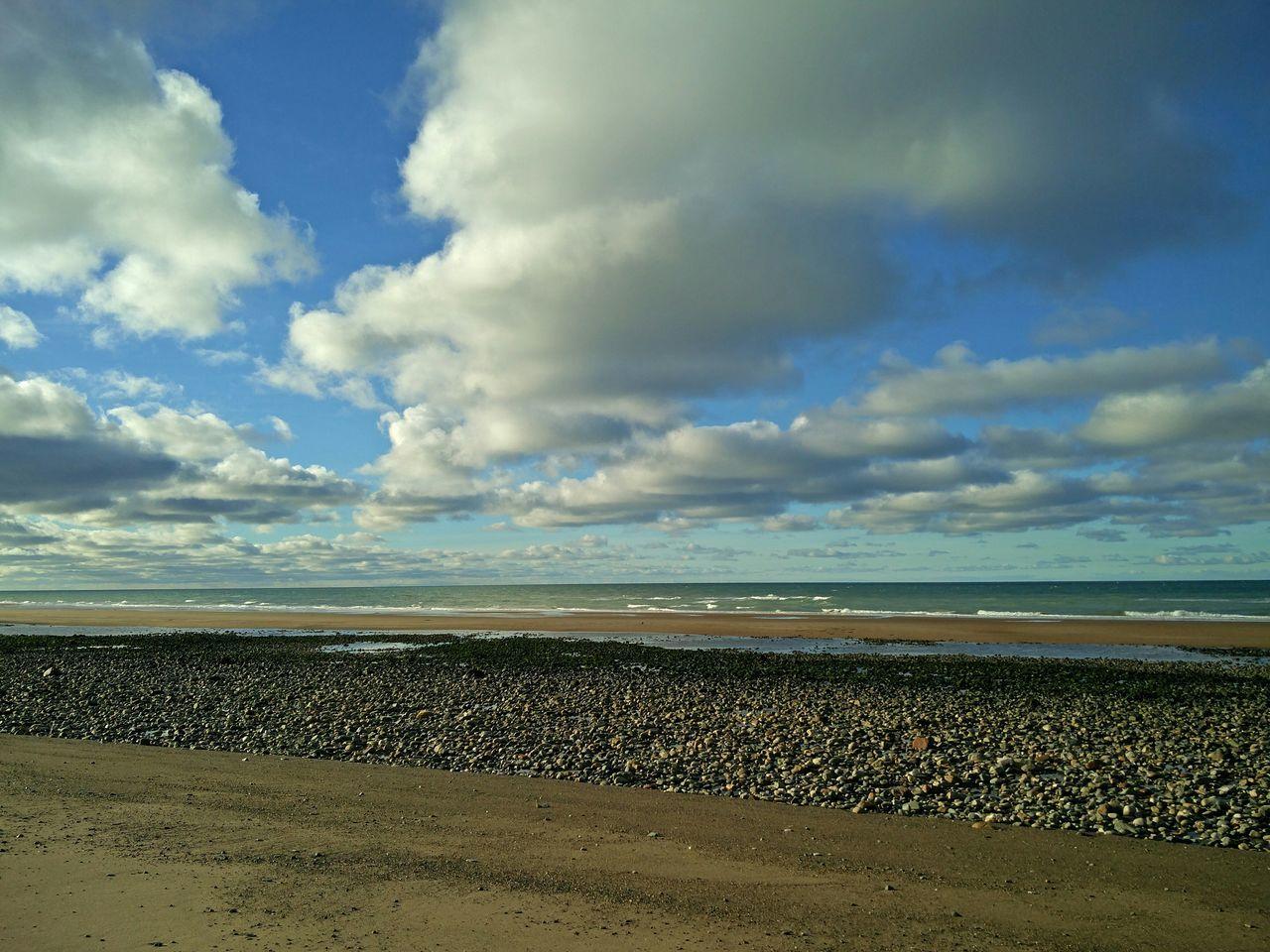 Beach By Sea Against Cloudy Sky