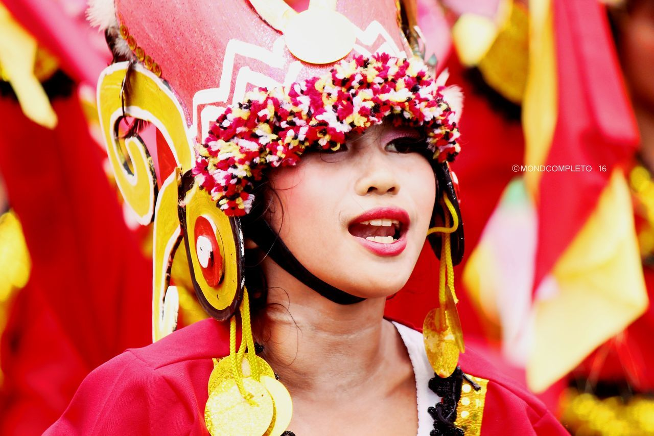 real people, one person, costume, lifestyles, young adult, front view, happiness, headshot, celebration, traditional clothing, smiling, focus on foreground, red, leisure activity, young women, day, outdoors, wearing, beautiful woman, multi colored, close-up